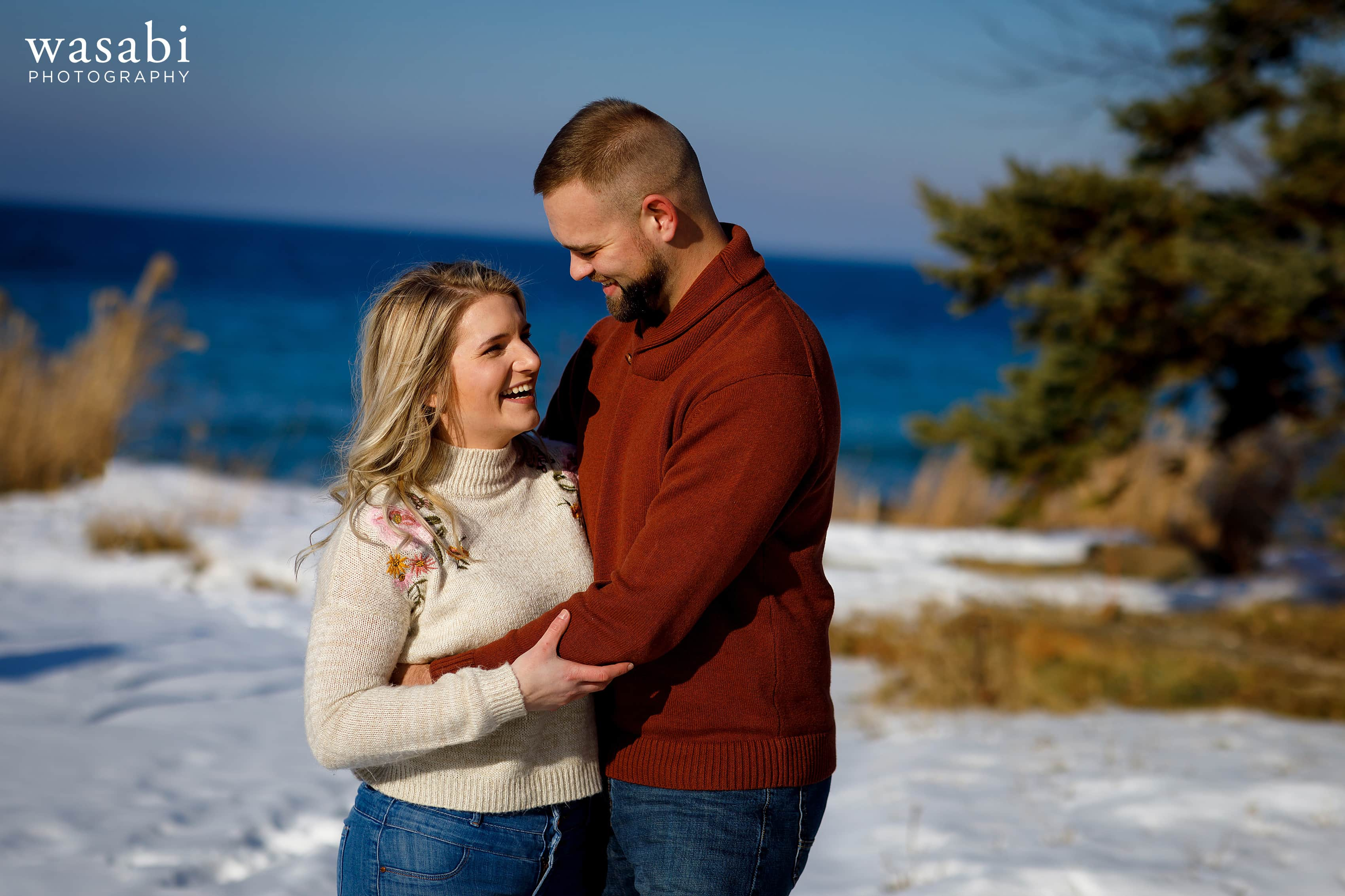engaged couple poses for engagement photo during winter engagement session with Lake Michigan in the background