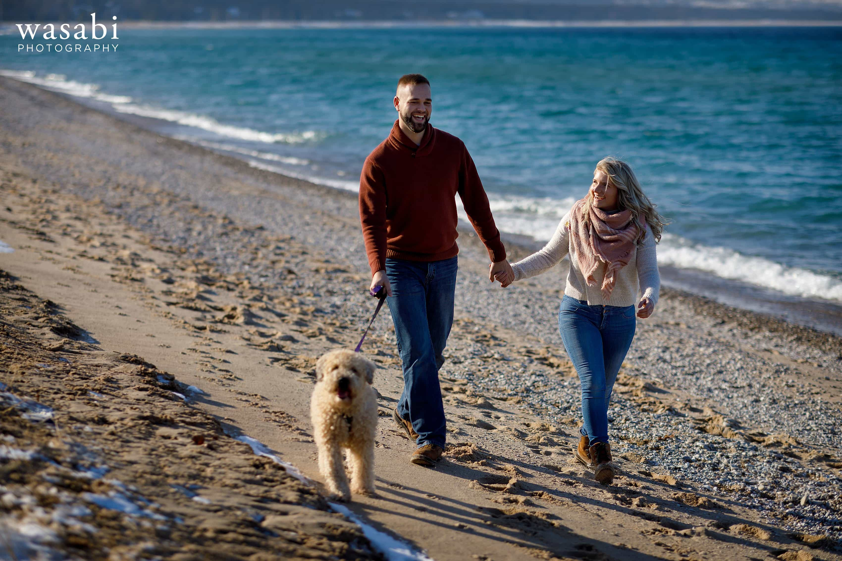 engaged couple walks their dog along the beach on Lake Michigans Sleeping Bear Bay in Glen Arbor Michigan during a winter engagement session