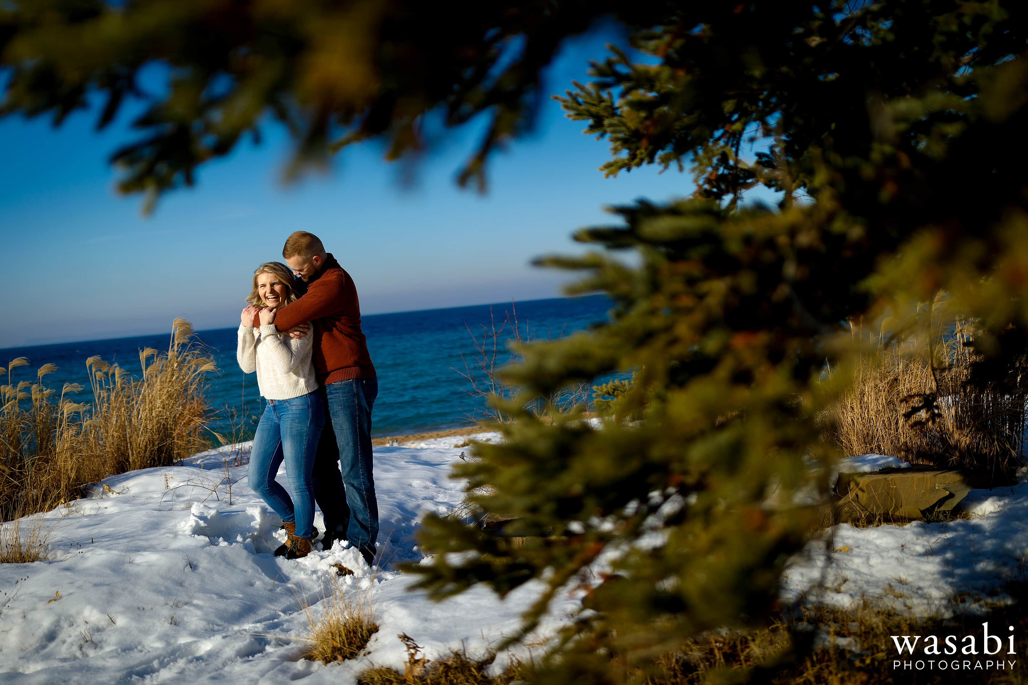 engaged couple walks their dog along the beach on Lake Michigans Sleeping Bear Bay in Glen Arbor during a northern Michigan winter engagement session