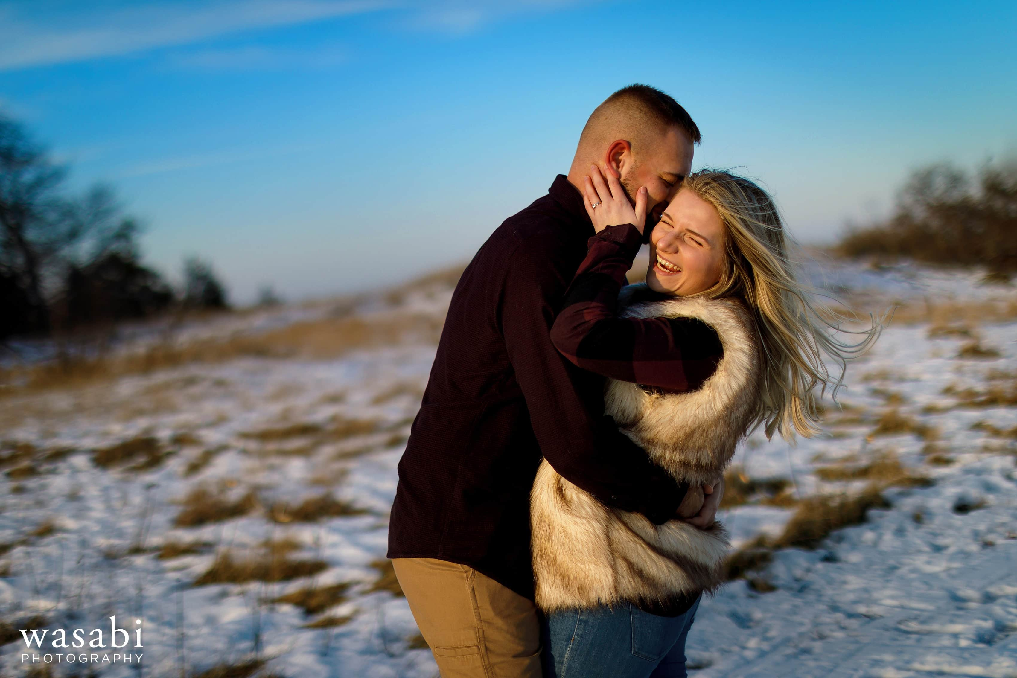 real moment of couple laughing during during winter engagement session in Glen Arbor Michigan