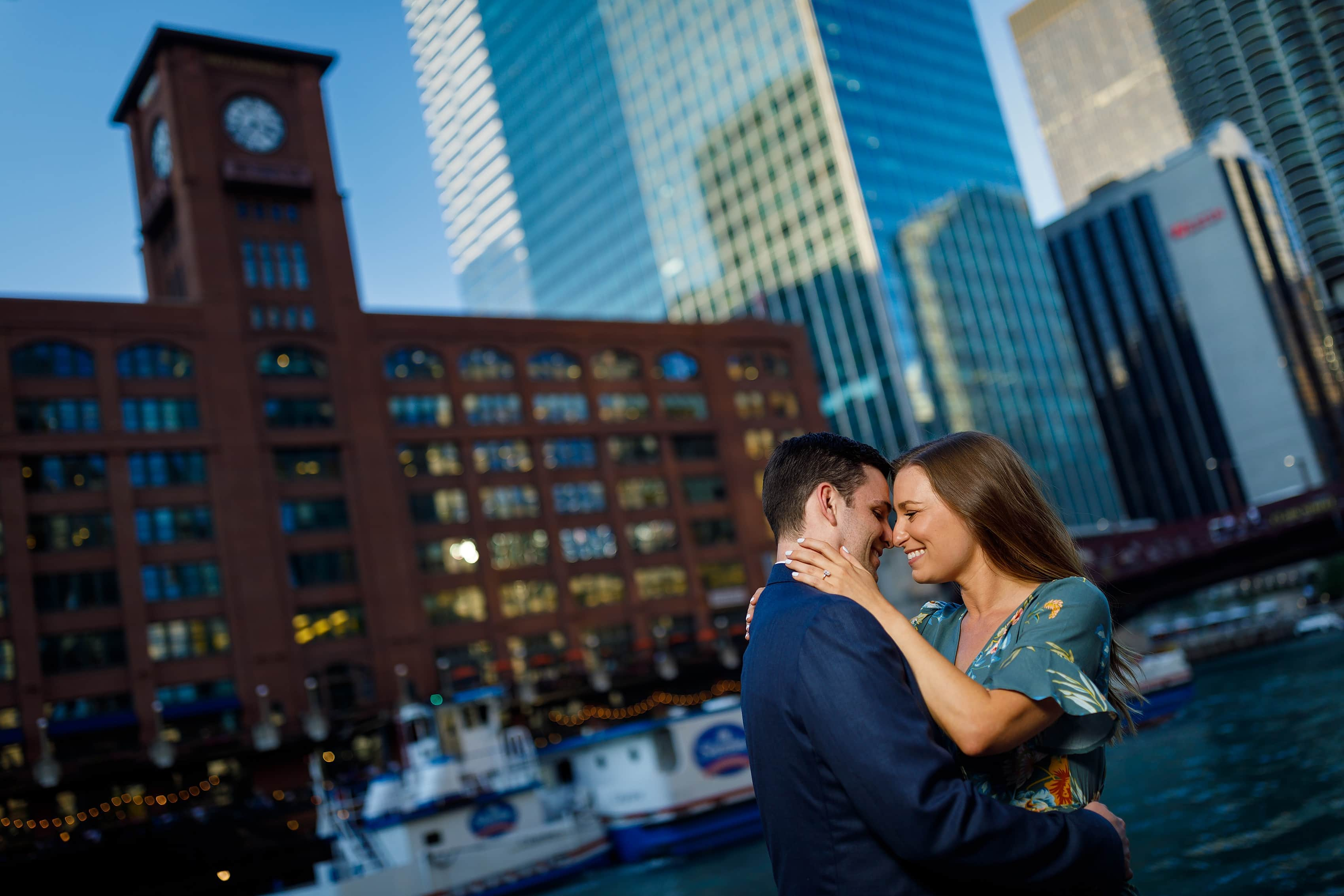 Couple poses for engagement photo along Chicago Riverwalk with Reid, Murdoch & Co. Building in the background