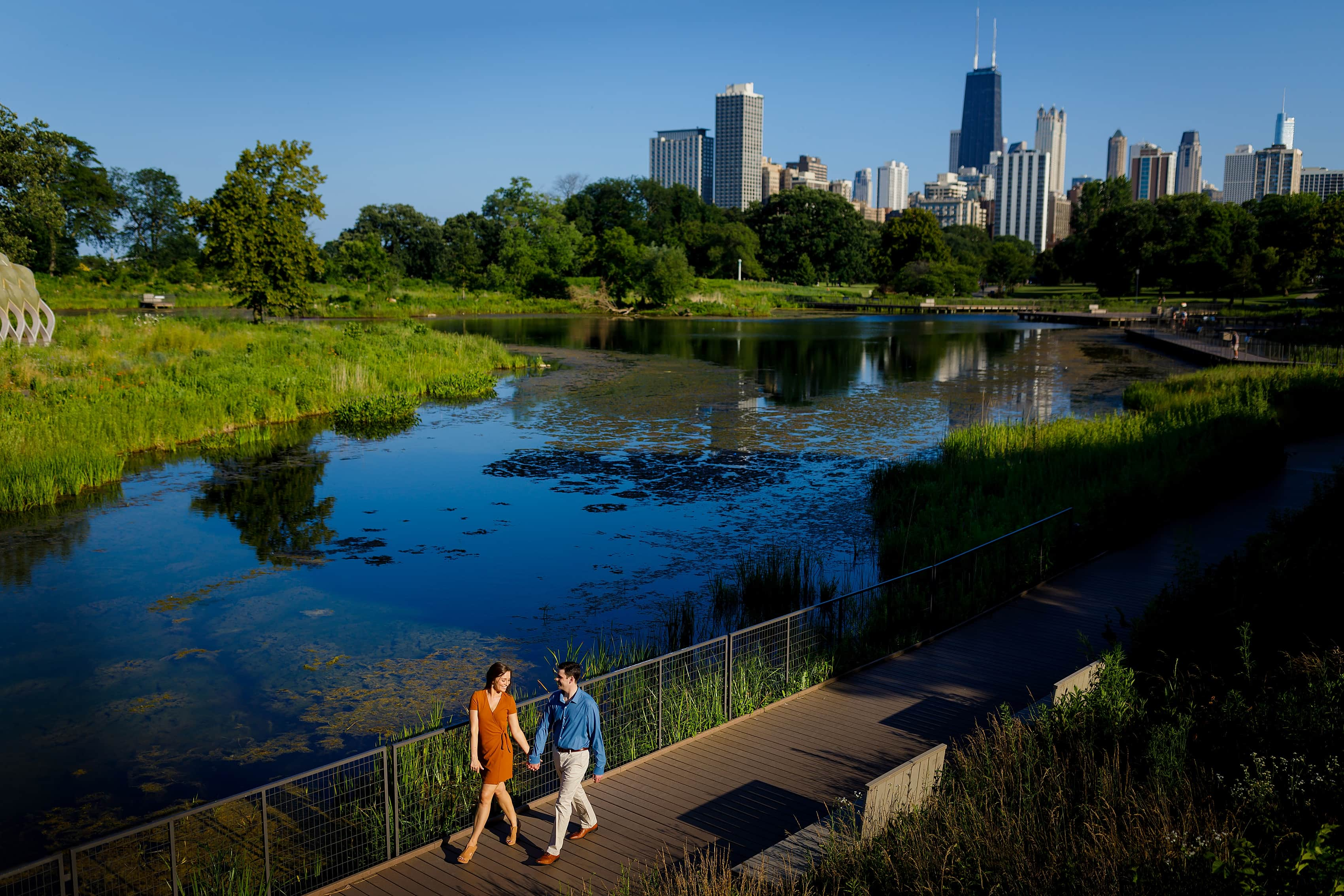 couple walks along South Pond boardwalk for Lincoln Park engagement photos with Chicago skyline in the background