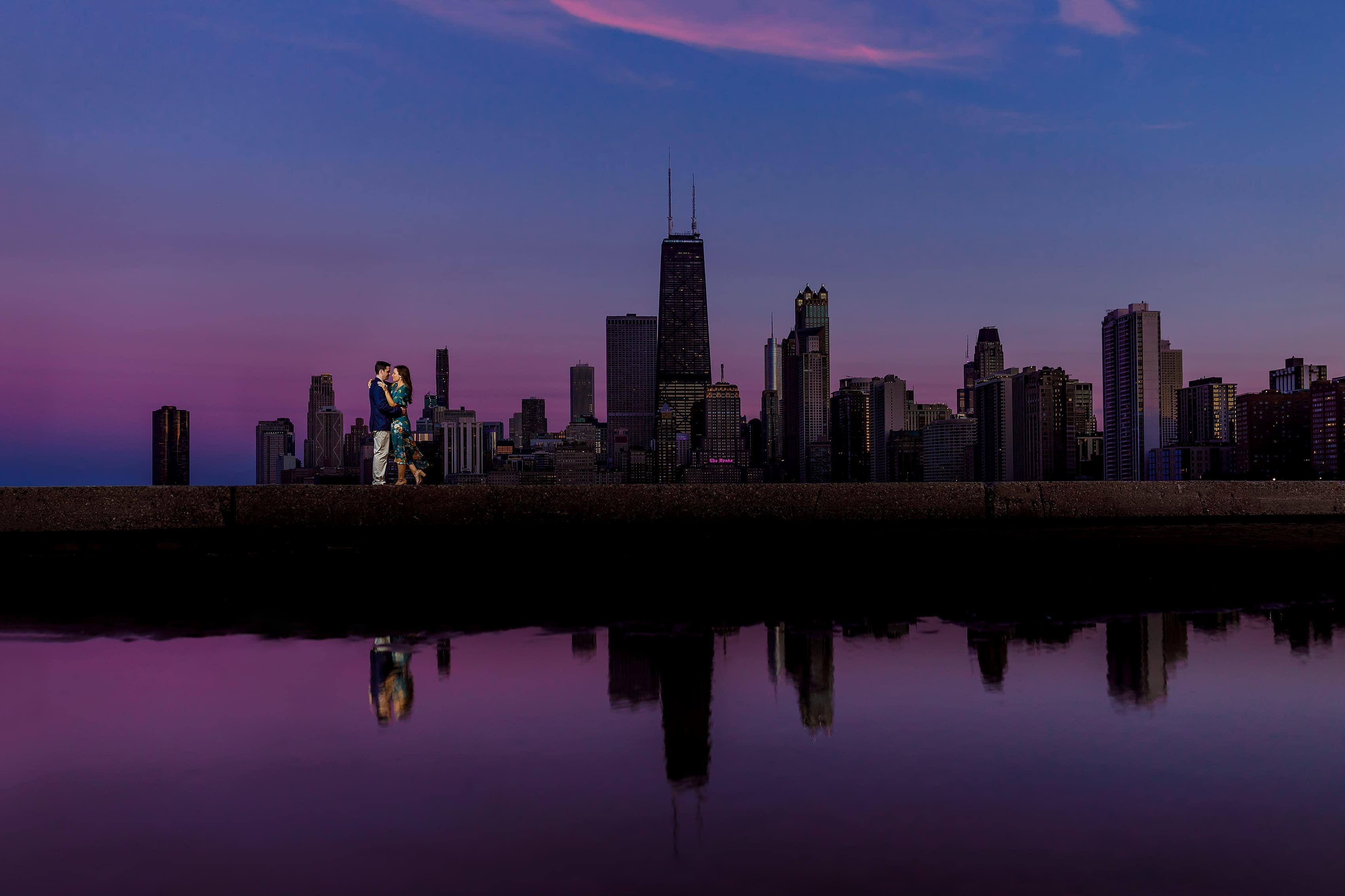 couple poses for well lit engagement photo at dusk at North Ave. Beach in Chicago with purple skies and reflection