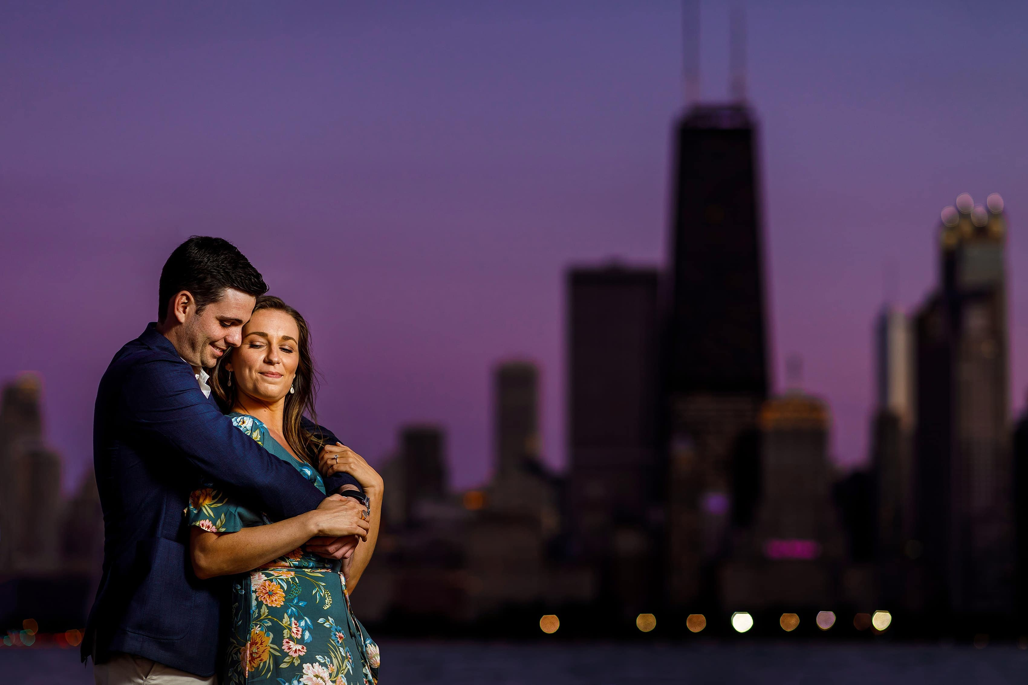 couple poses for lit engagement photo at dusk at North Ave. Beach in Chicago with purple skies