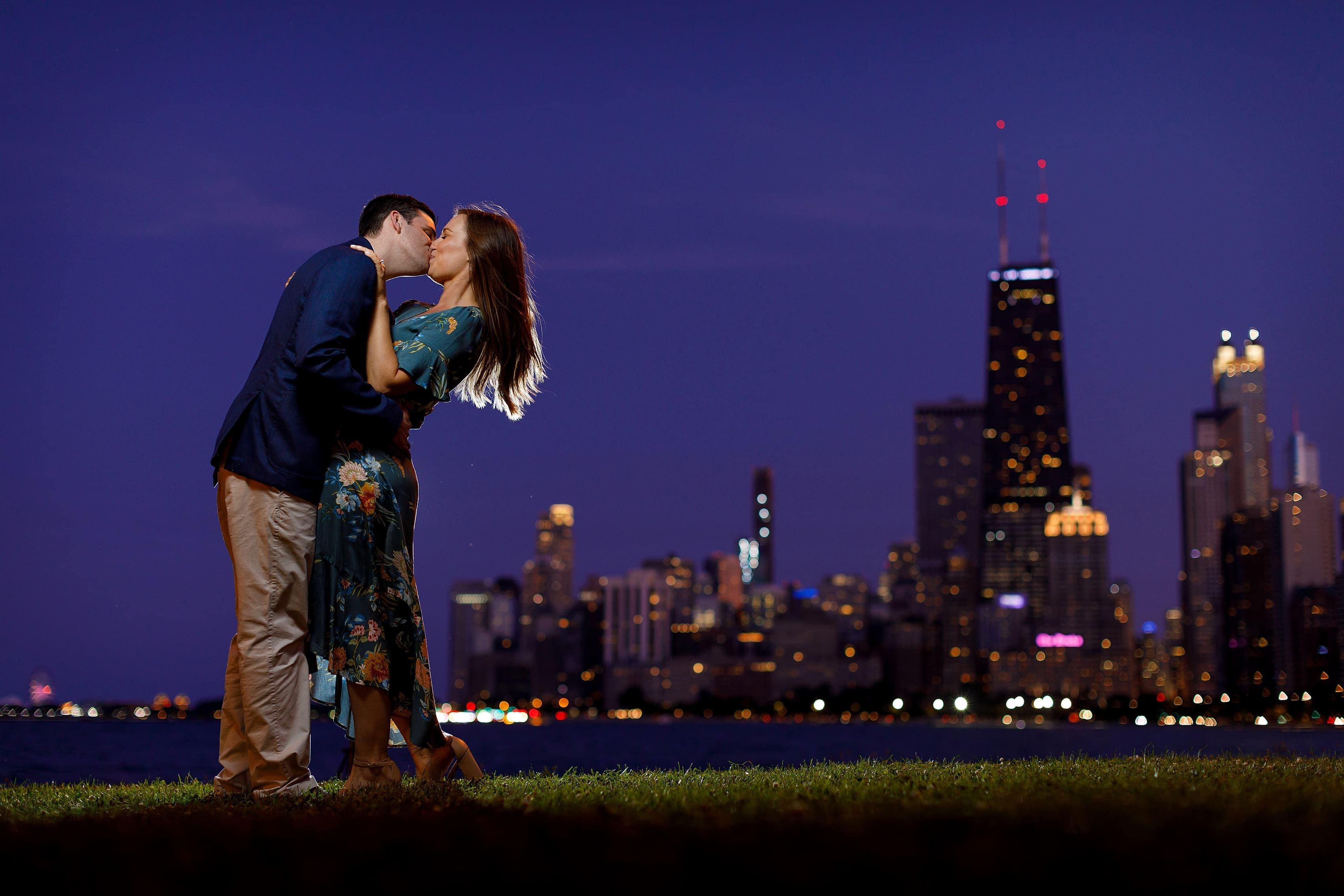 couple poses for backlit engagement photo at dusk at North Ave. Beach in Chicago with purple skies and skyline in the background