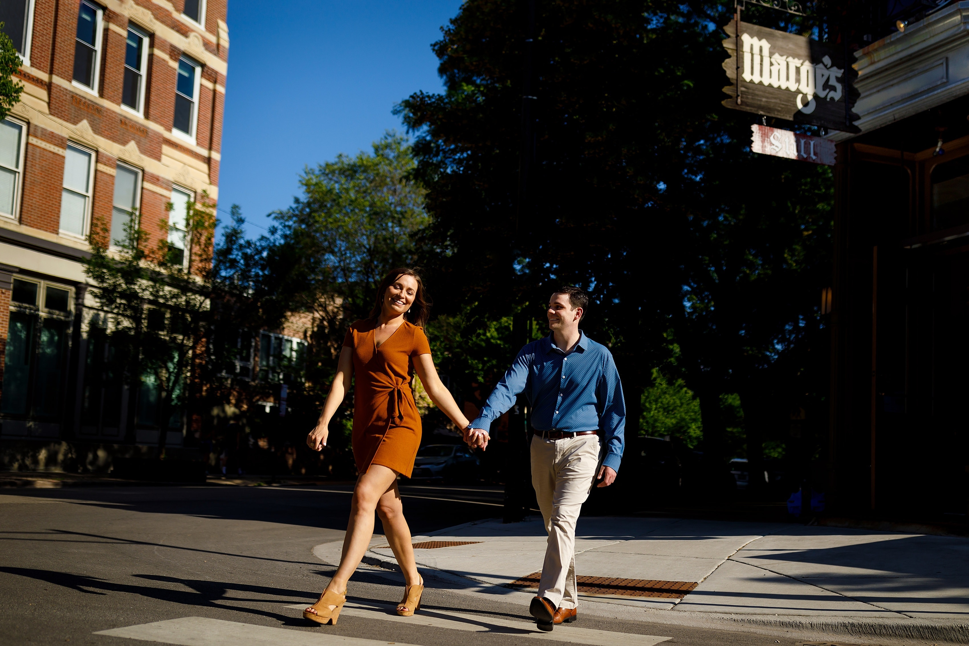 Couple walks across street during engagement photos in Chicago's Old Town neighborhood at Marge's Still