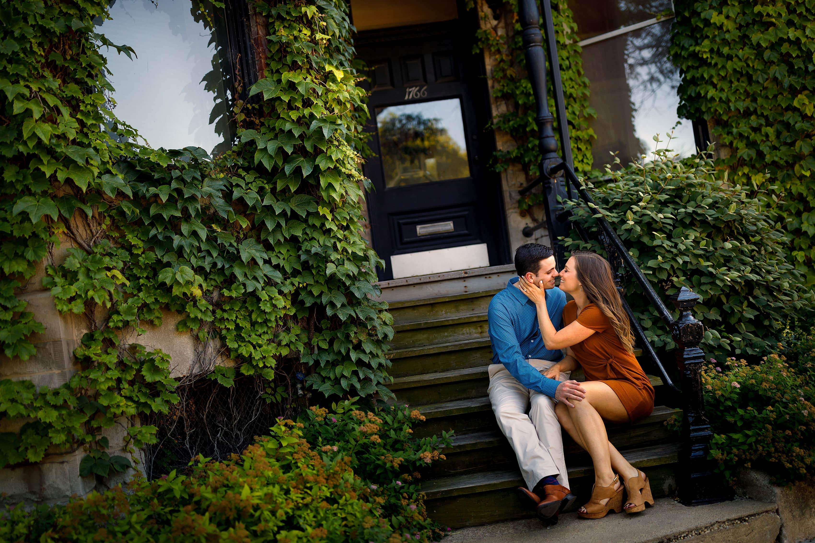Couple sits on stairs outside house with Ivy in Chicago's Old Town neighborhood during engagement session