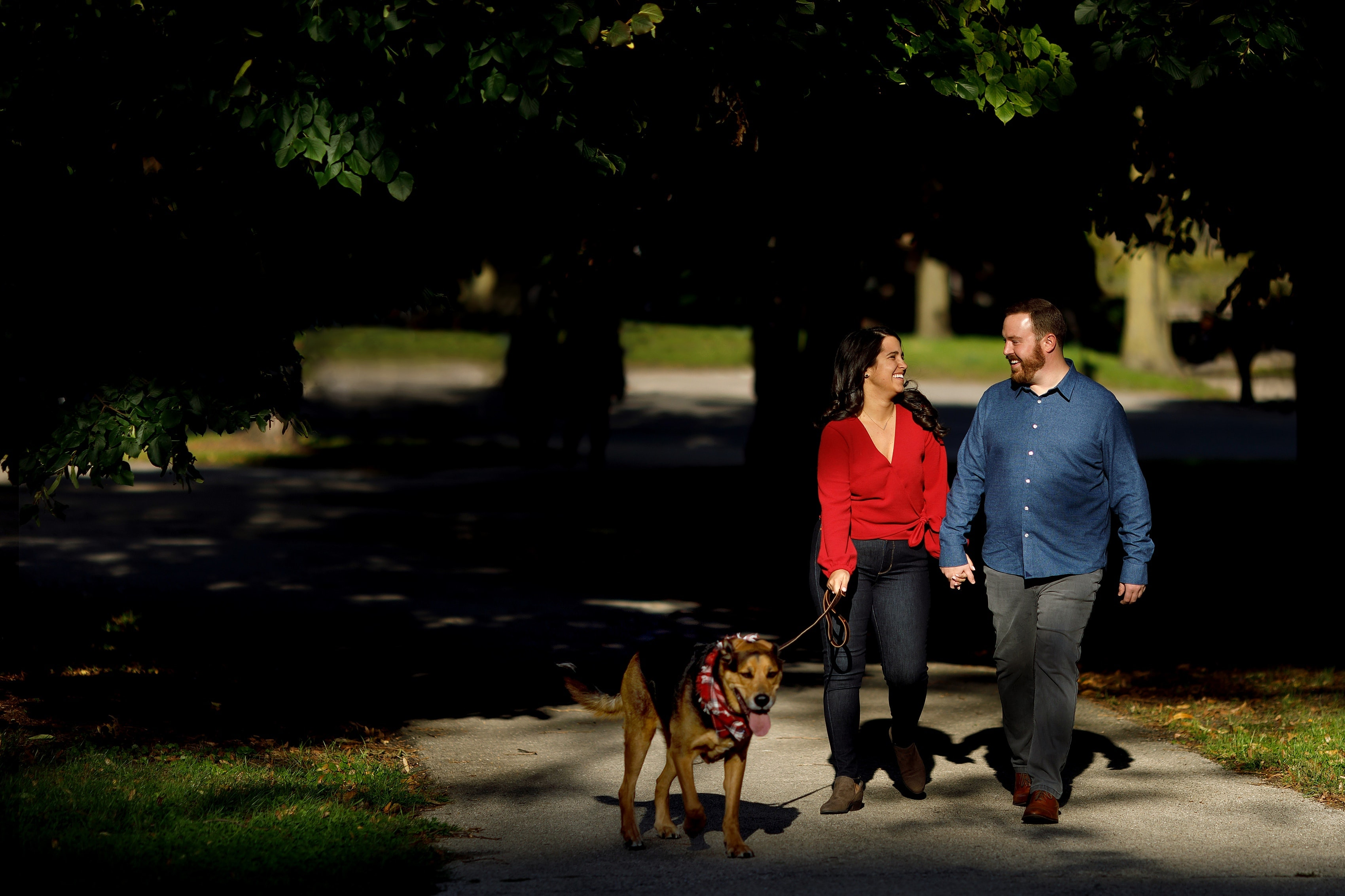couple walks with their dog through Lincoln Park in Chicago during fall season engagement session