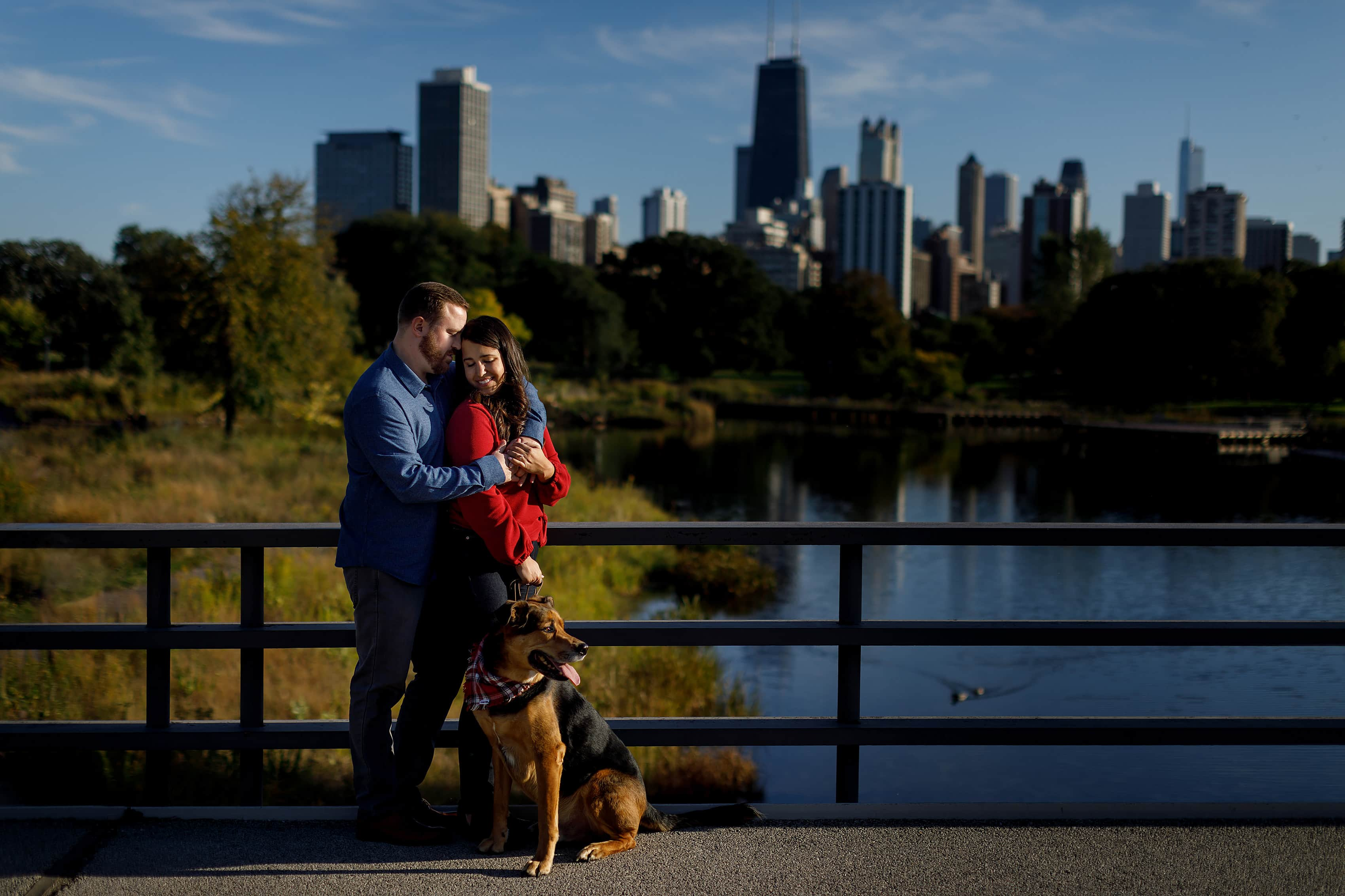 couple poses with their dog on the bridge Lincoln Park in Chicago during fall season engagement session with Chicago Skyline in the background