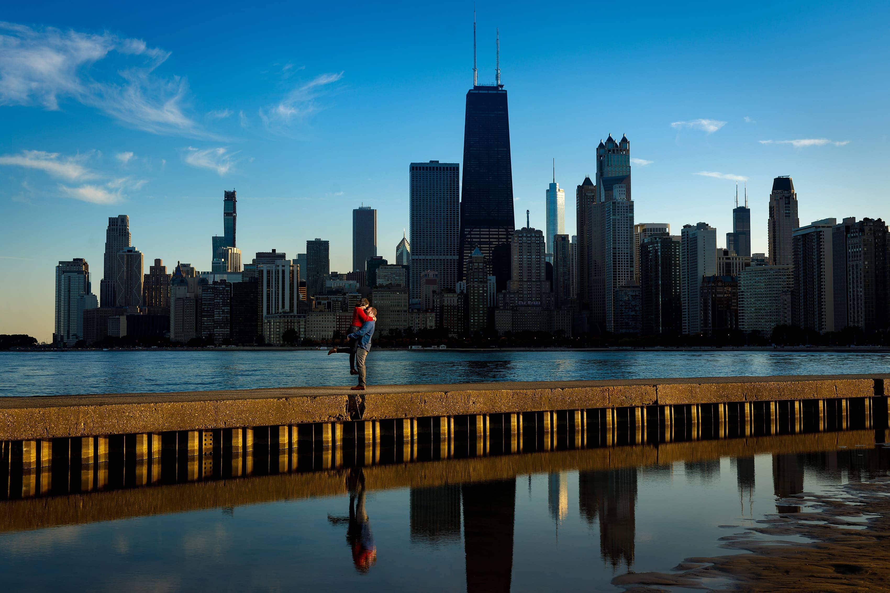 couple poses for engagement photo along Lake Michigan at North Avenue Beach with Chicago skyline in the background