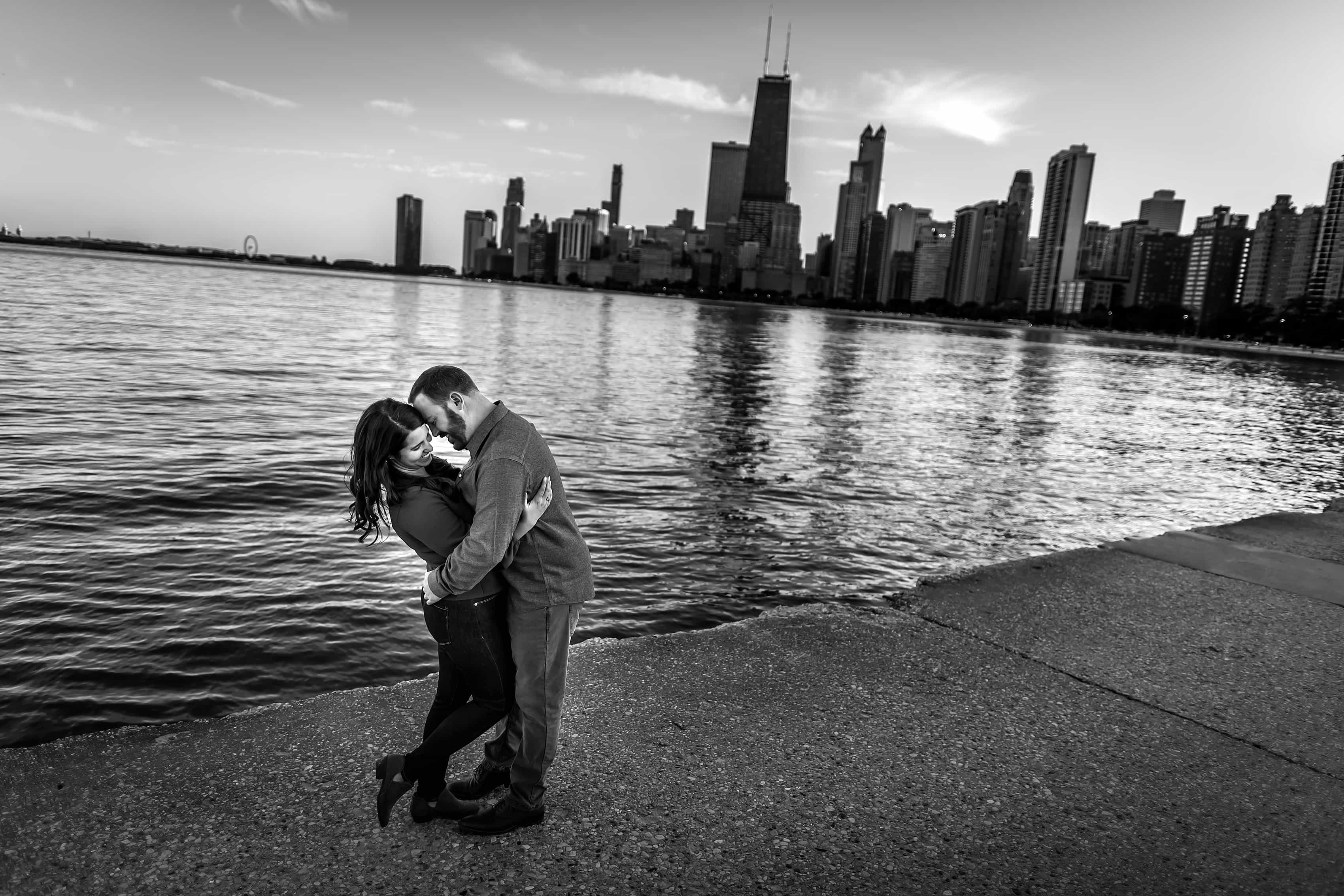 couple laughs during engagement session along Lake Michigan at North Avenue Beach with Chicago skyline in the background