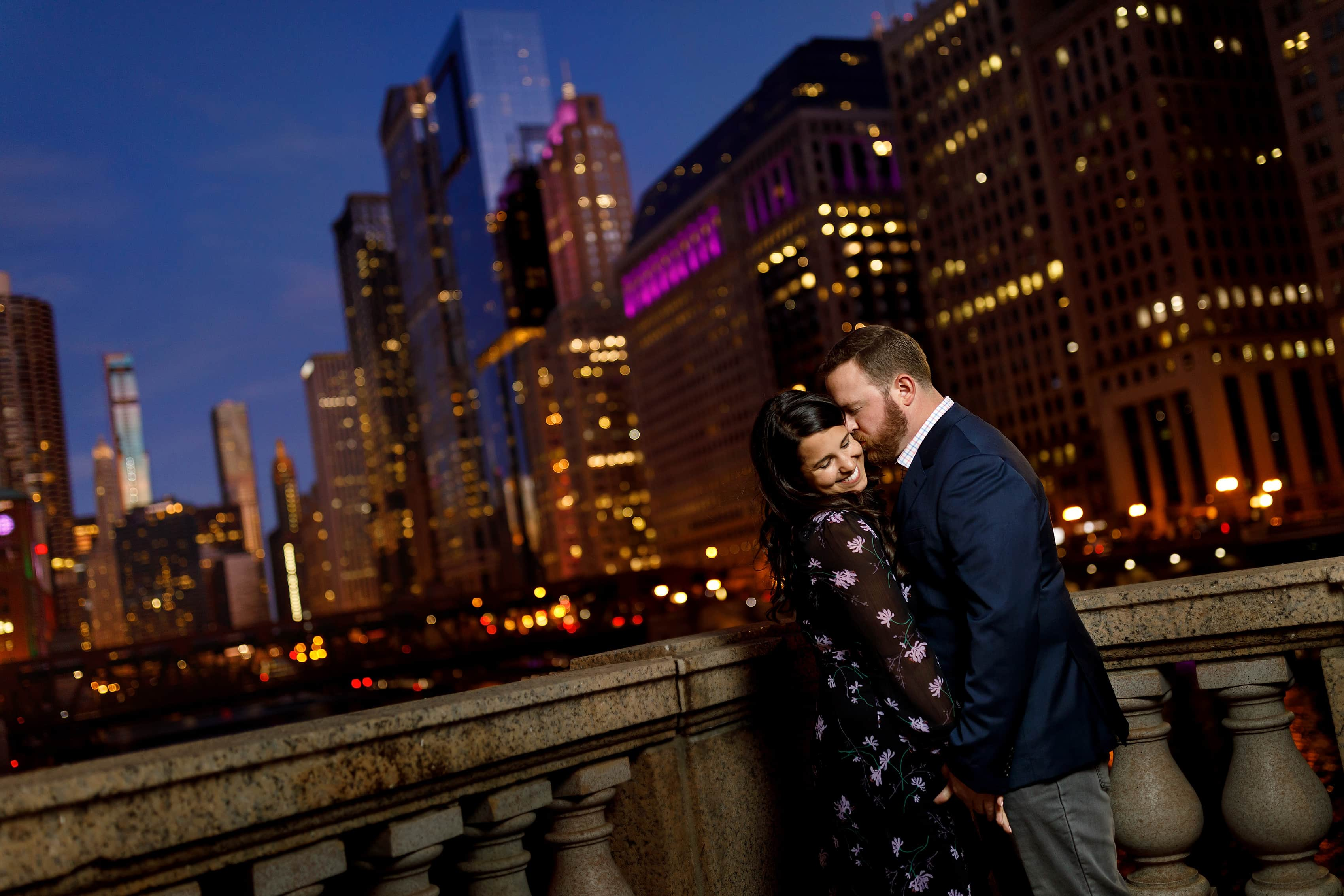 groom gives bride a kiss on the cheek during downtown Chicago engagement session on the river with skyline in the background during twilight blue hour