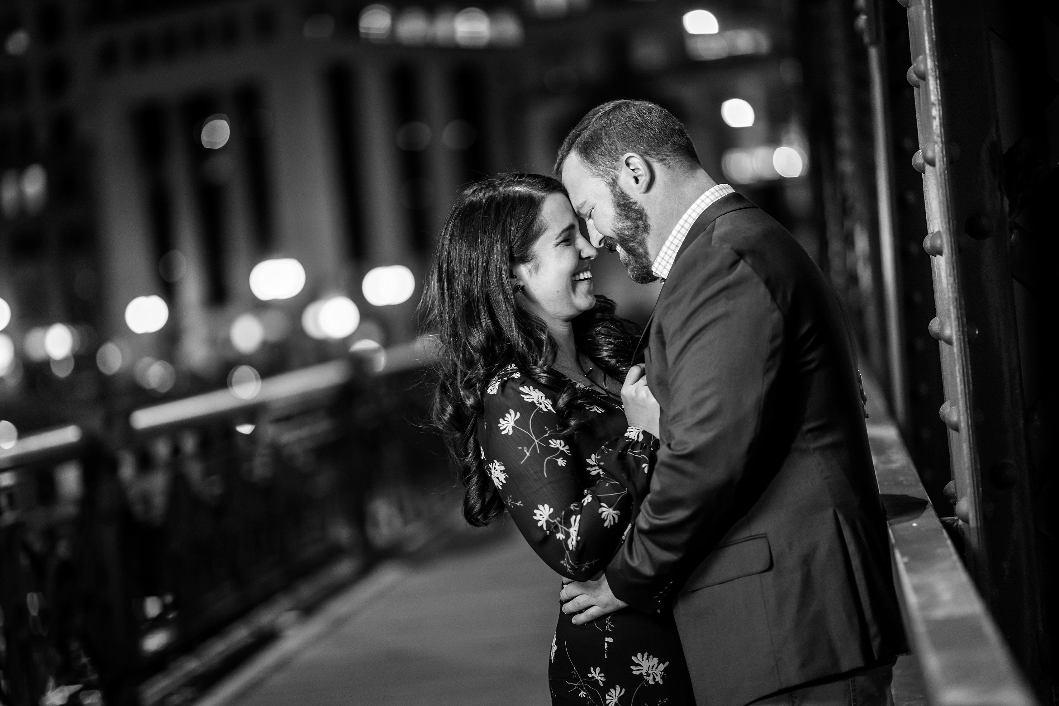 black and white night photo of bride and groom laughing during engagement session on downtown Chicago bridge