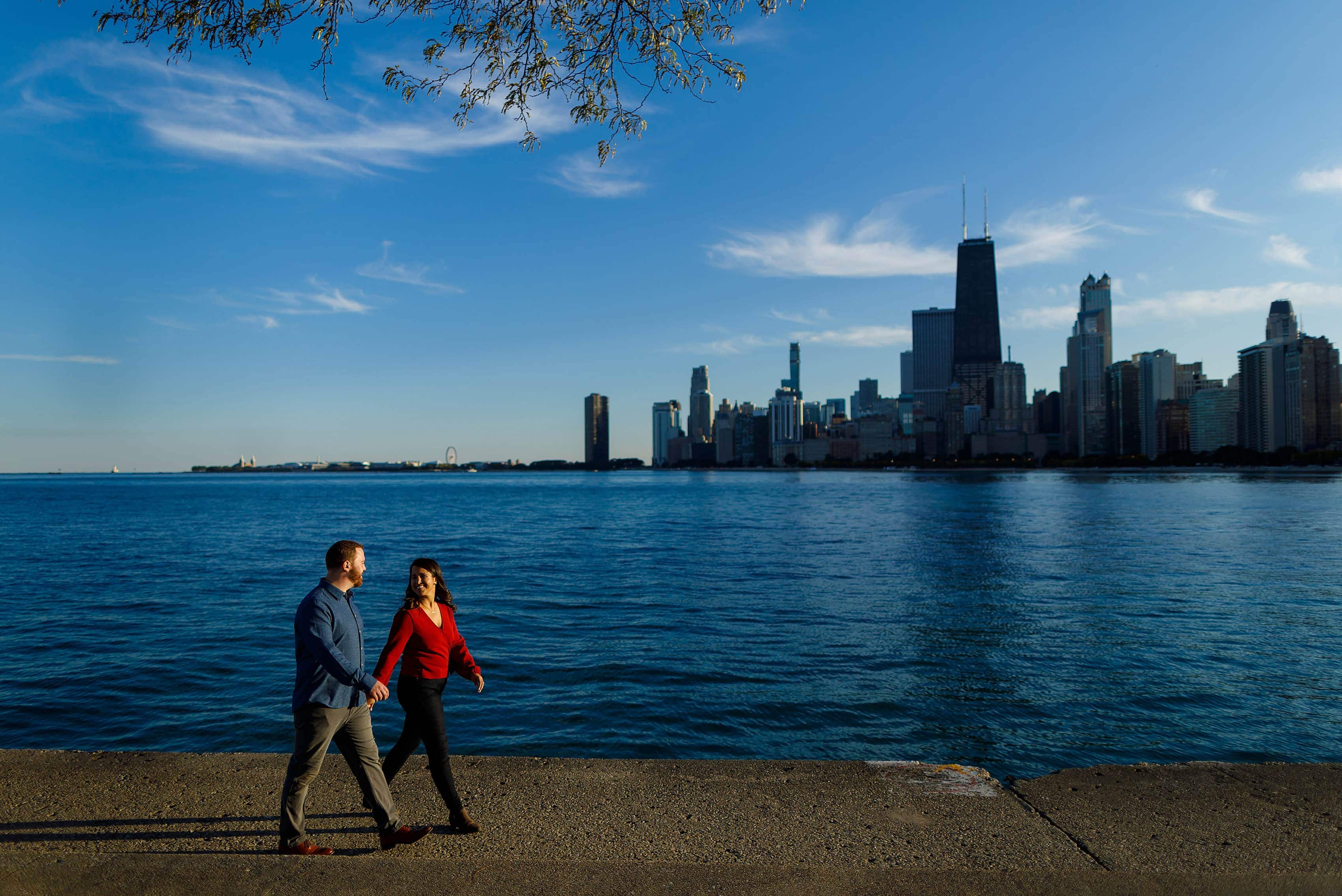 couple walks along Lake Michigan at North Avenue Beach with Chicago skyline in the background during fall engagement session