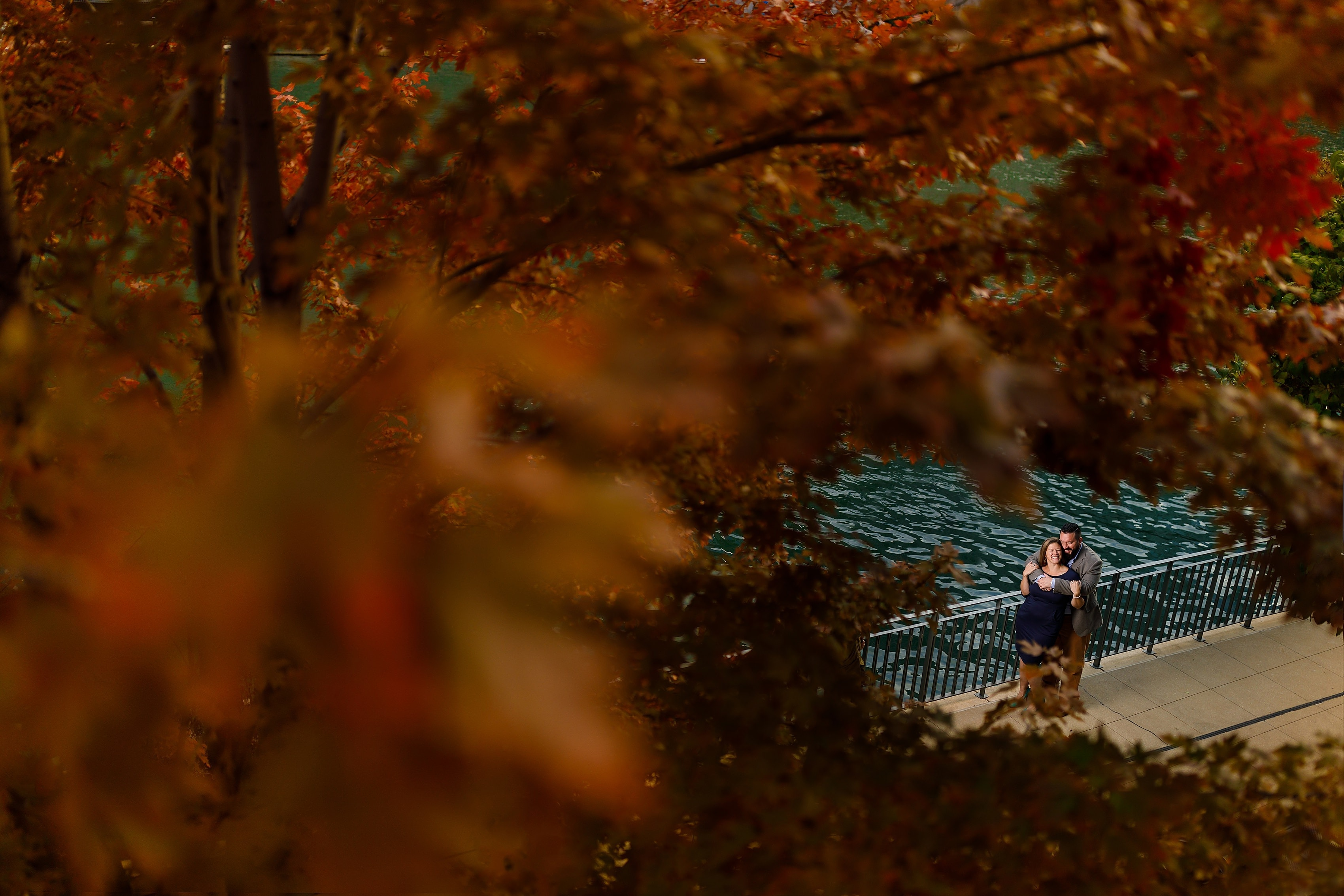 Orange tree fall color engagement photo with couple laughing on Chicago River in downtown Chicago