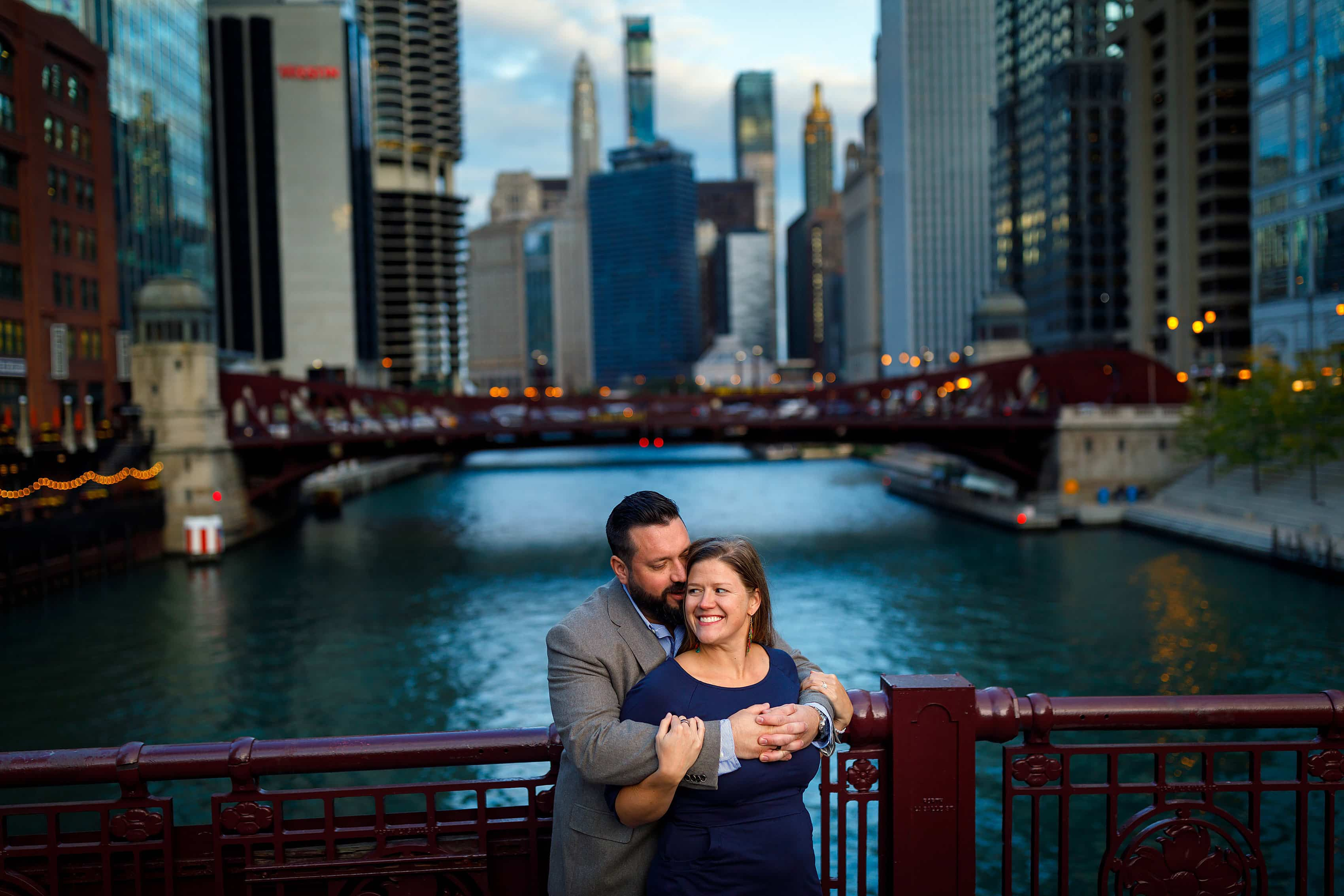 Couple poses for engagement photo on LaSalle Street bridge in downtown Chicago with the river and skyline in the background