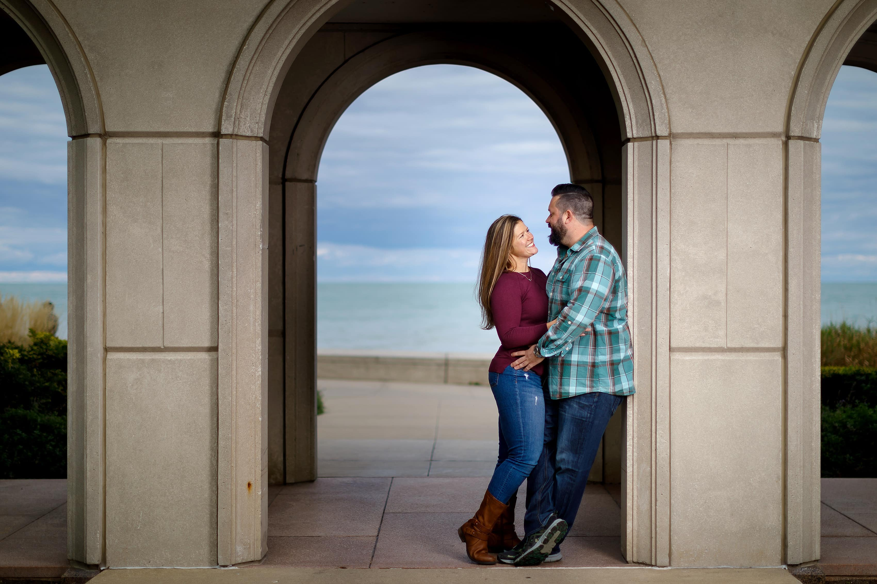 couple poses for engagement photo under arched walkway with Lake Michigan in the background on the campus of Loyola University Chicago