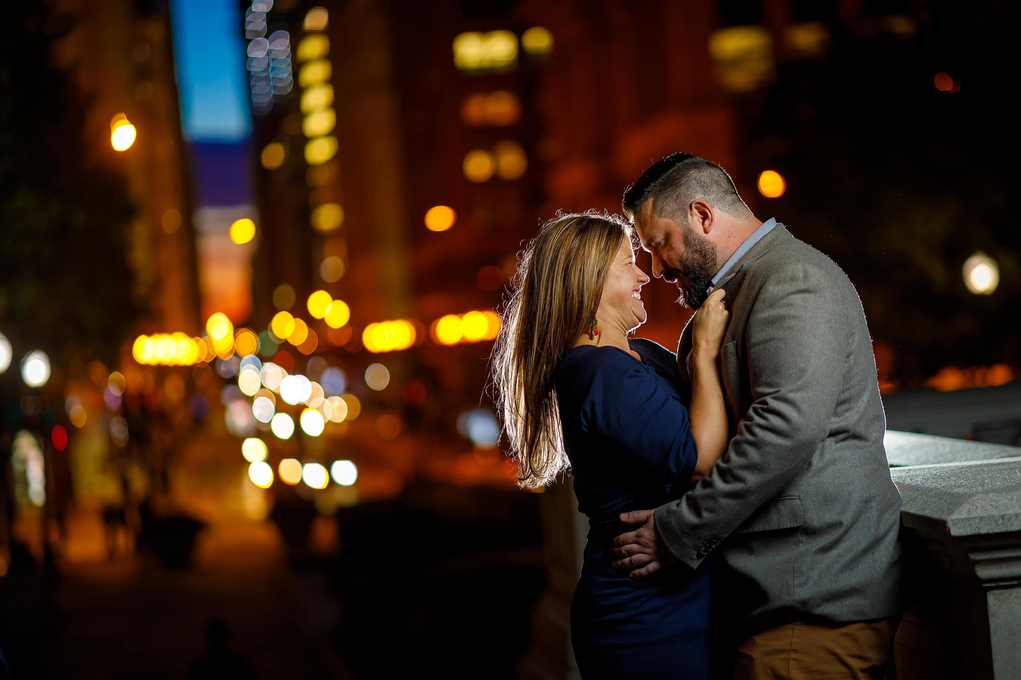 couple laughs during night engagement photo at Millennium Park in Chicago