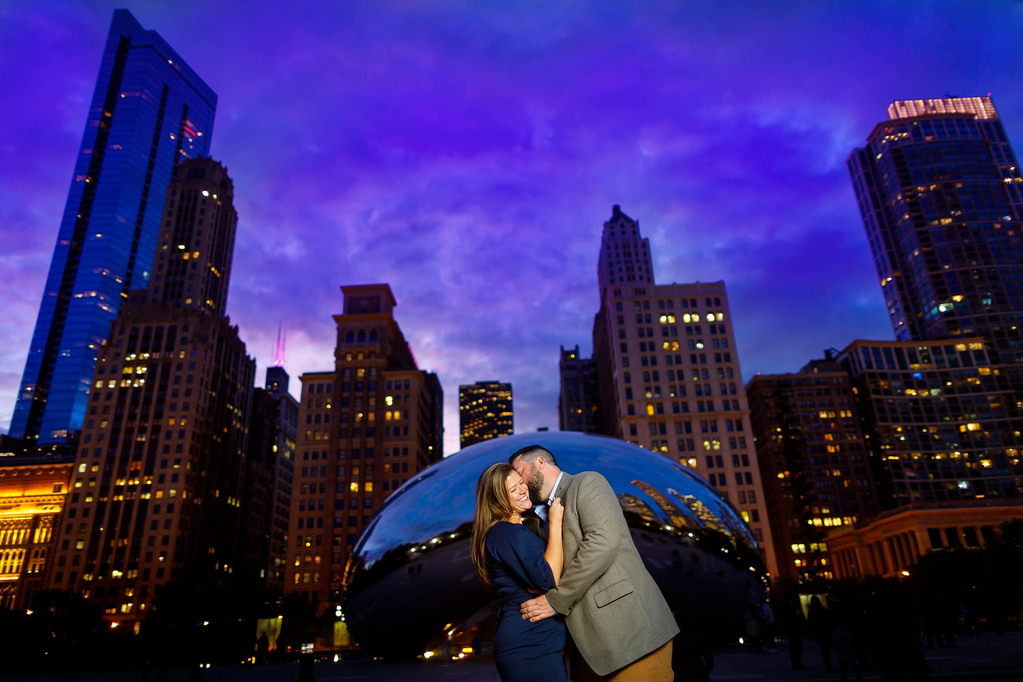 couple kisses during engagement session at Millennium Park with Cloudgate The Bean statue in the background and Chicago skyline