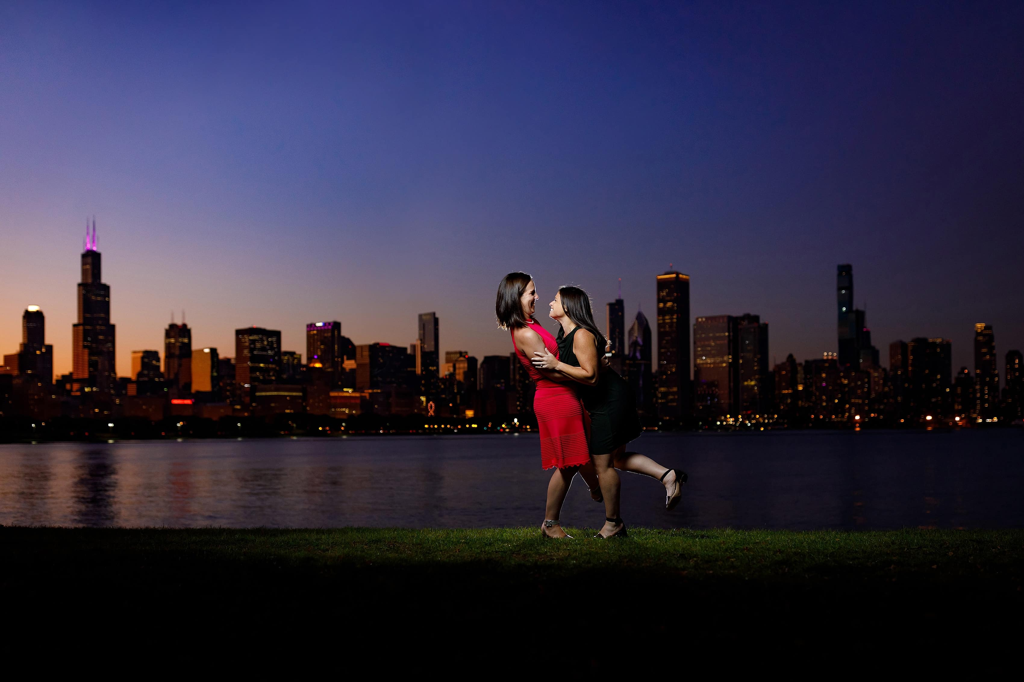 Couple laughs with skyline in the background during night engagement session at Adler Planetarium on Chicago's museum campus