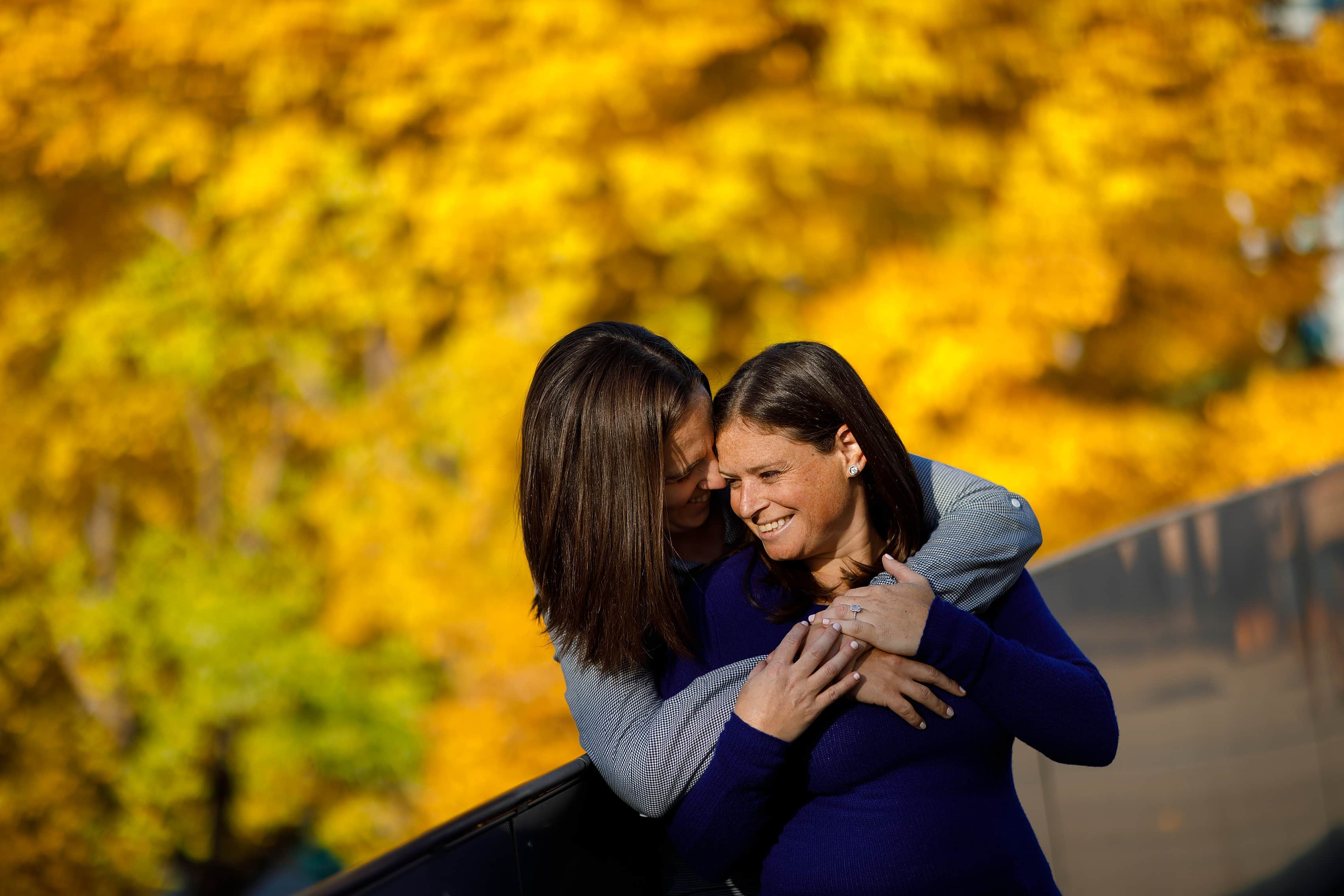 Couple hugs in front of bright yellow leaves during engagement session at Maggie Daley Park in downtown Chicago