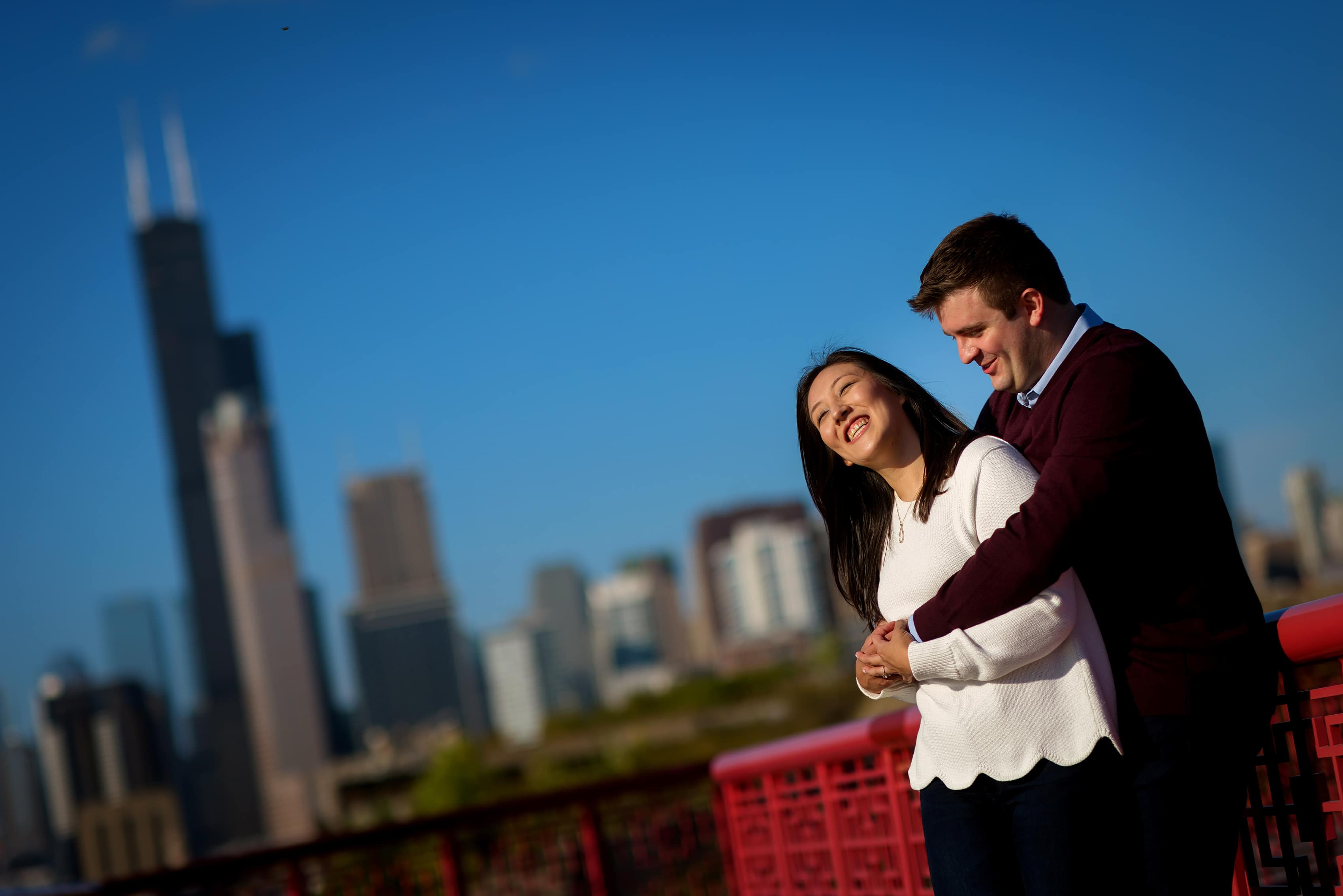Couple poses for engagement photos at Ping Tom Memorial Park in Chicago's Chinatown neighborhood with the skyline in the background