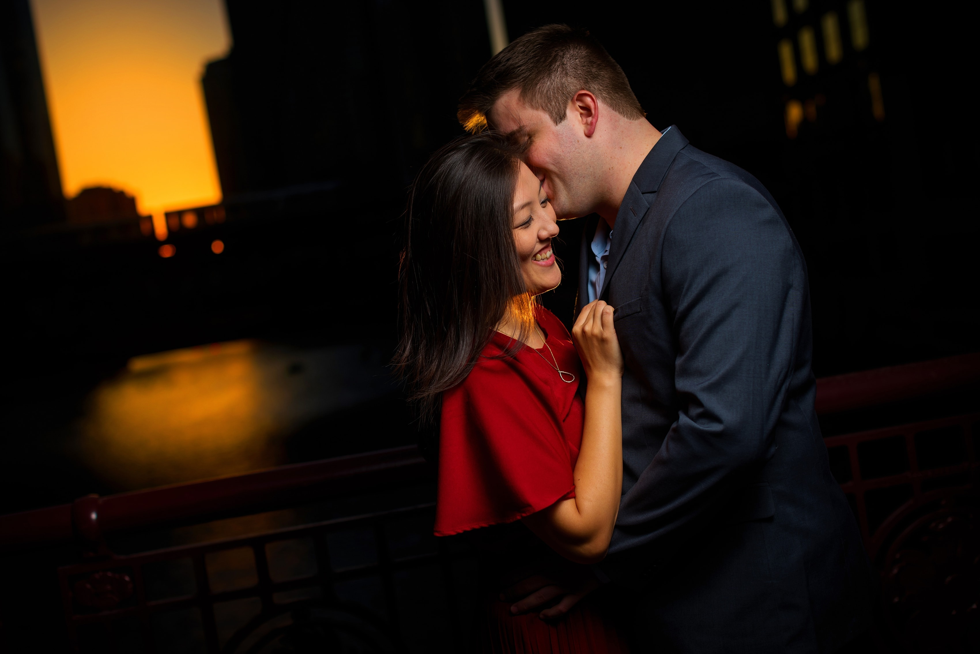 Couple poses for engagement photos along riverwalk with the sun setting in the background in downtown Chicago