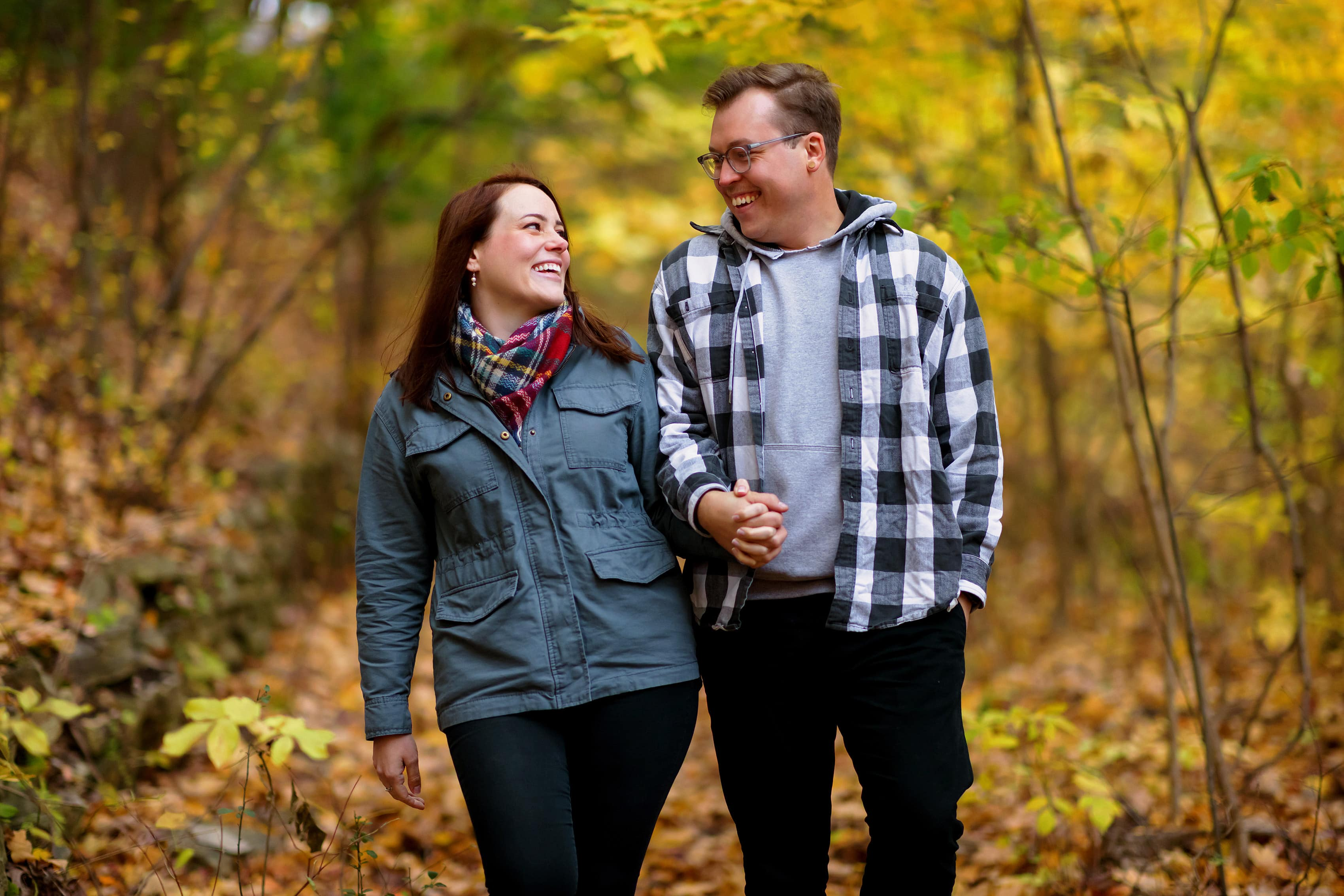 couple walks through woods holding hands during engagement session at Rosewood Park in Highland Park, Illinois
