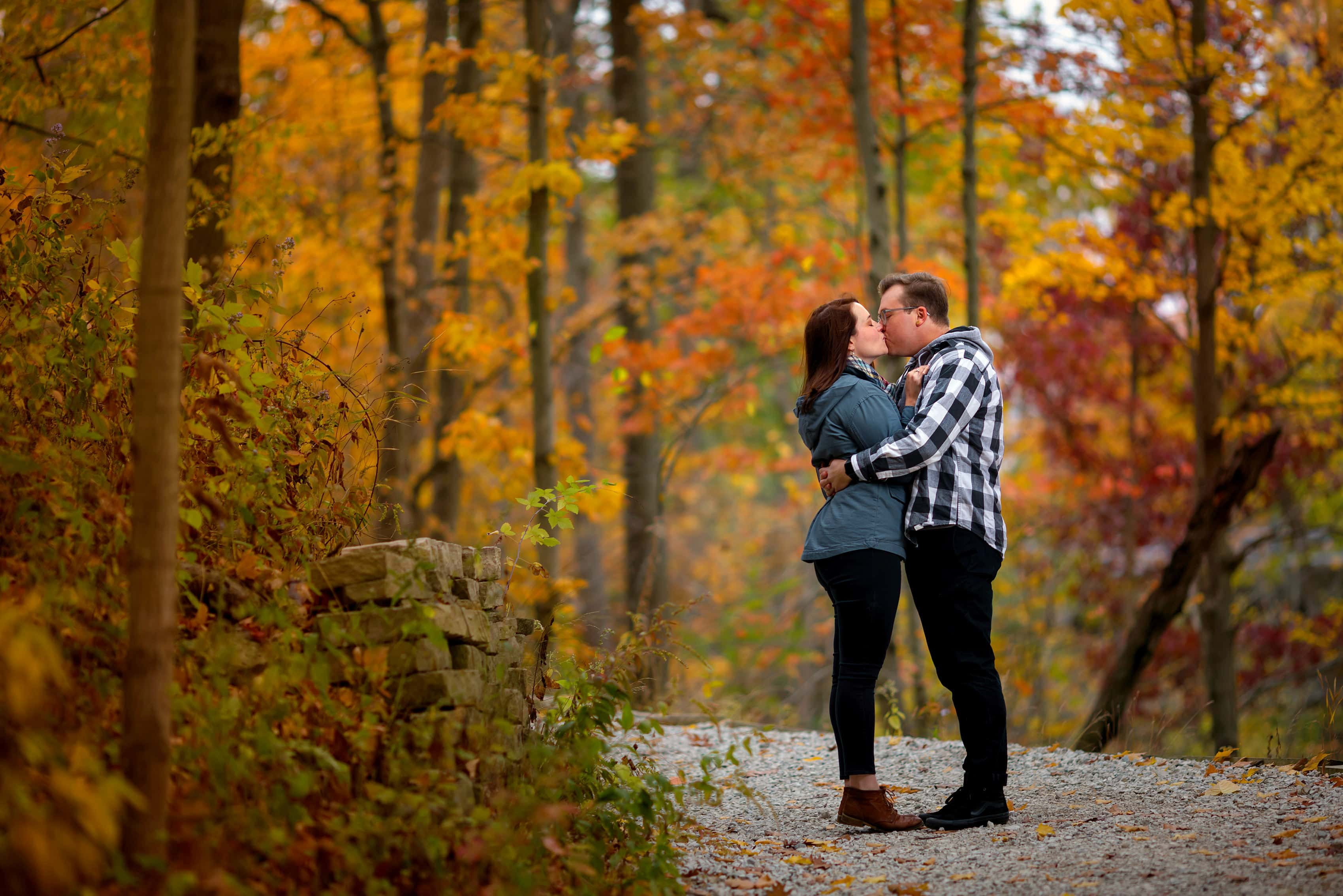 couple kisses with colorful trees in the background during engagement session at Rosewood Park in Highland Park, Illinois