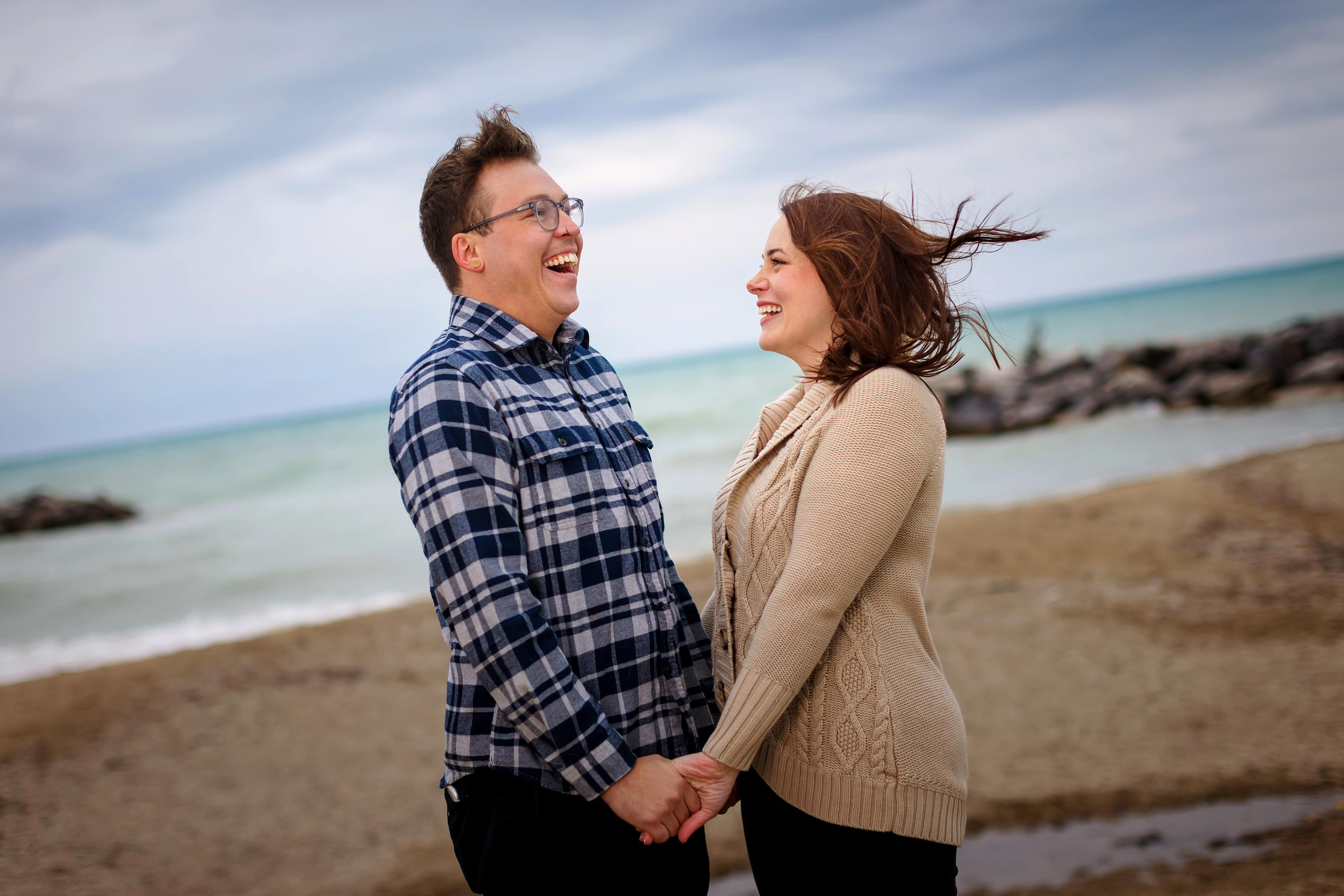 couple laughs on the beach during engagement session at Rosewood Beach in Highland Park, Illinois