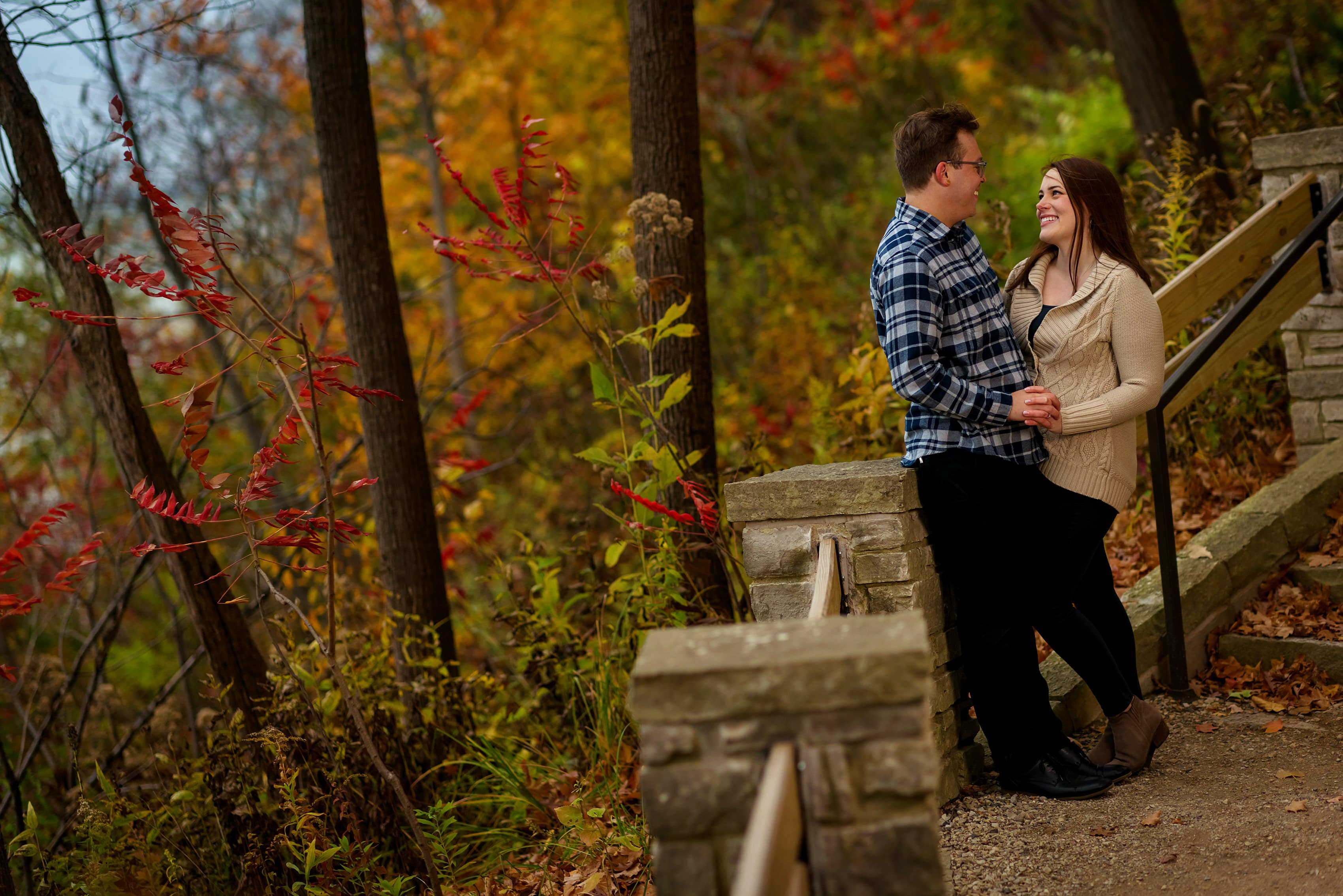 couple laughs on the shore during engagement session at Rosewood Beach in Highland Park, Illinois