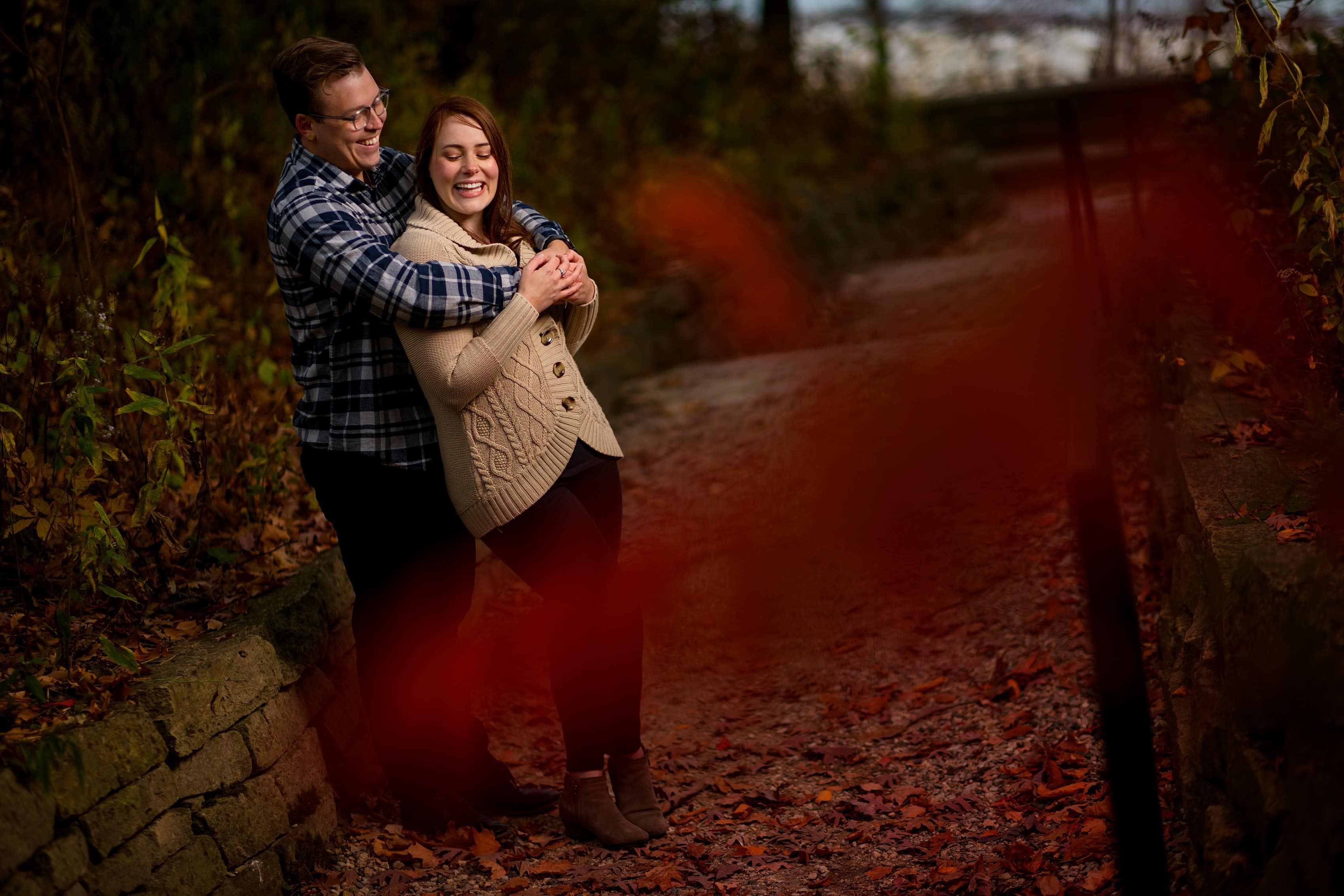 couple smiles with red leaves in front of the camera during engagement session at Rosewood Beach in Highland Park, Illinois