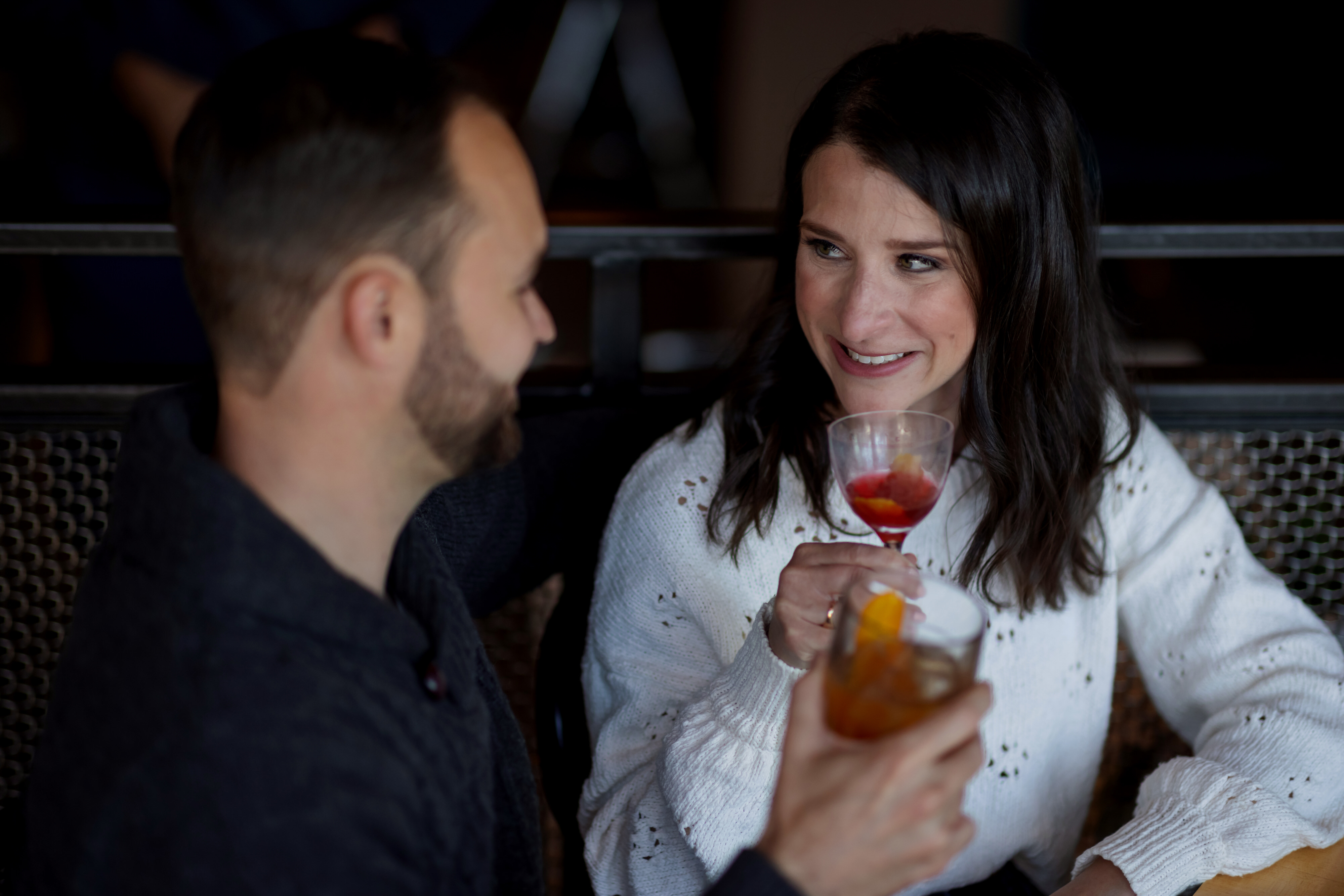 couple poses for engagement photos with drinks at Funkenhausen in Chicago