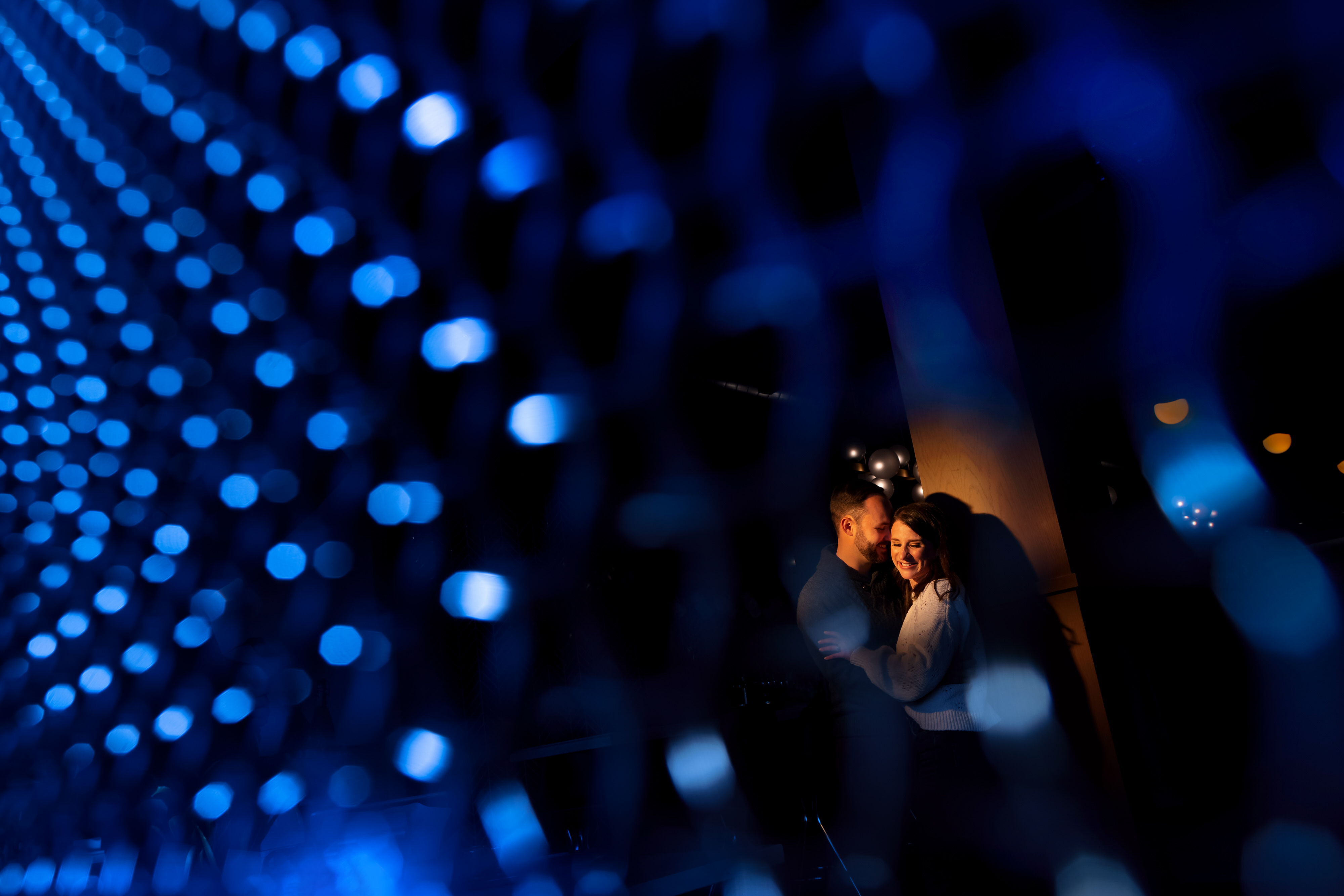 couple poses for engagement photos with blue specular highlights and orange spotlight at Funkenhausen in Chicago