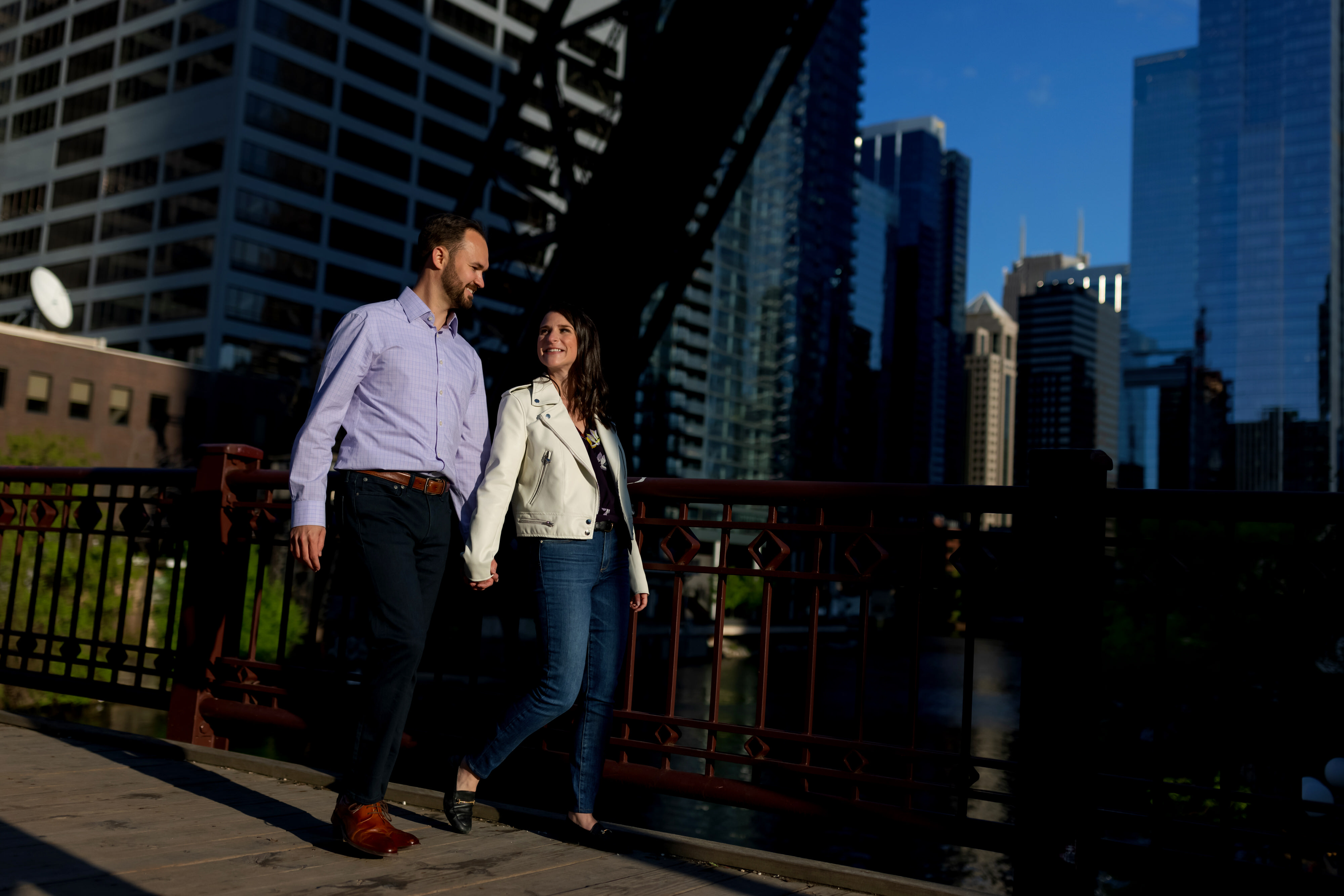 Couple walks across Kinzie Street Bridge with the Chicago skyline in the background during an engagement session