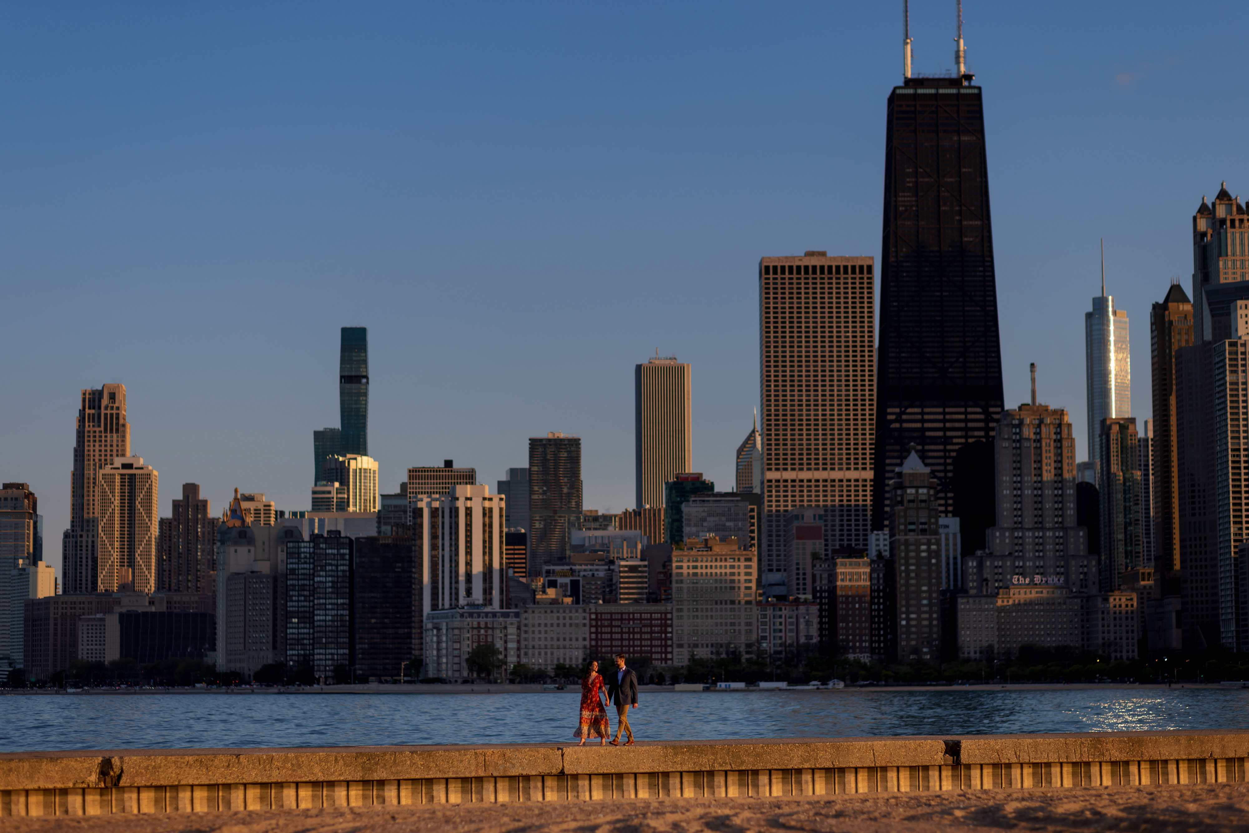 Couple walks along the pier at North Avenue Beach in Chicago's Old Town neighborhood during an engagement session