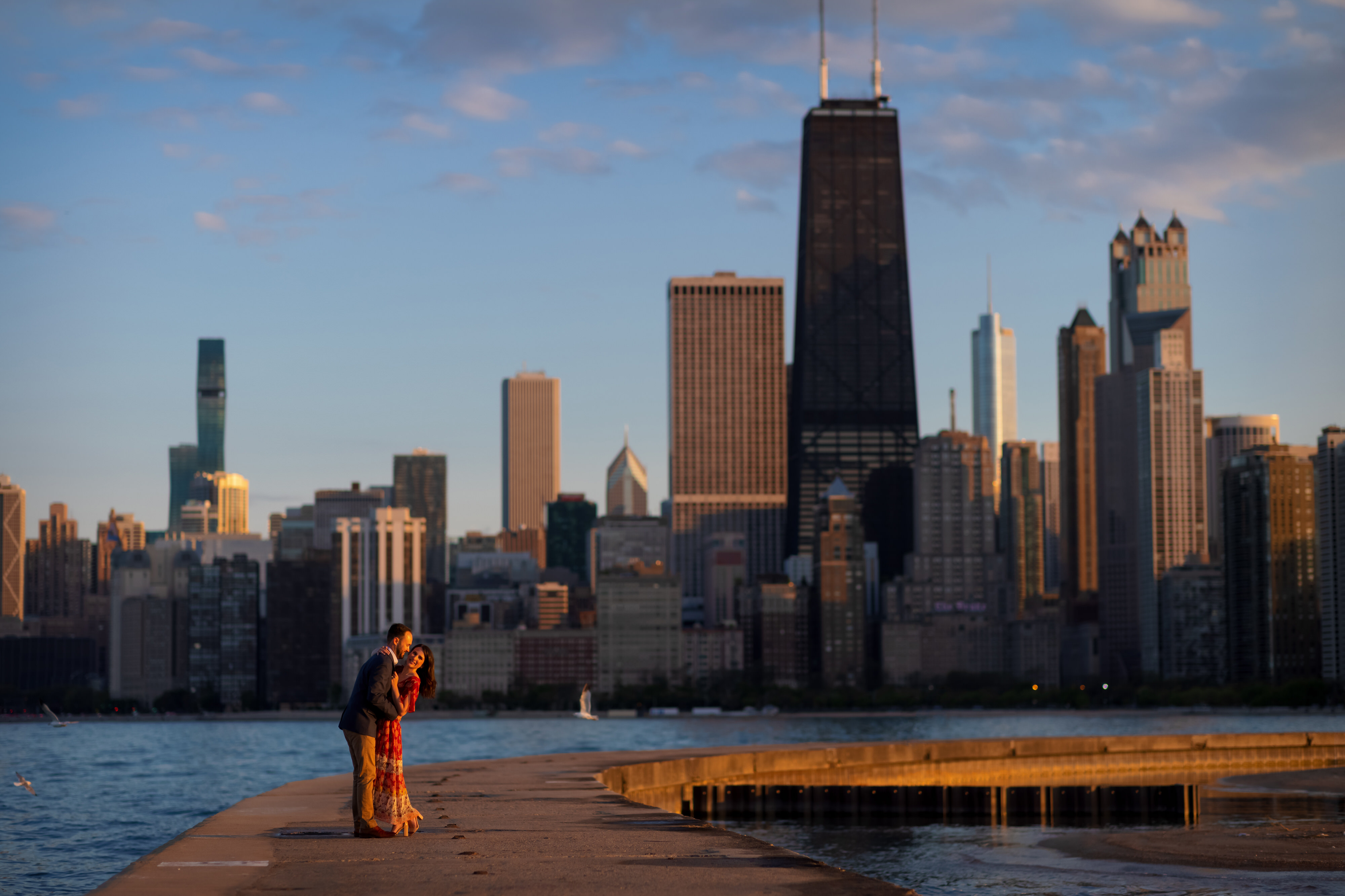 Couple poses for a portrait on the pier at North Avenue Beach in Chicago's Old Town neighborhood during an engagement session