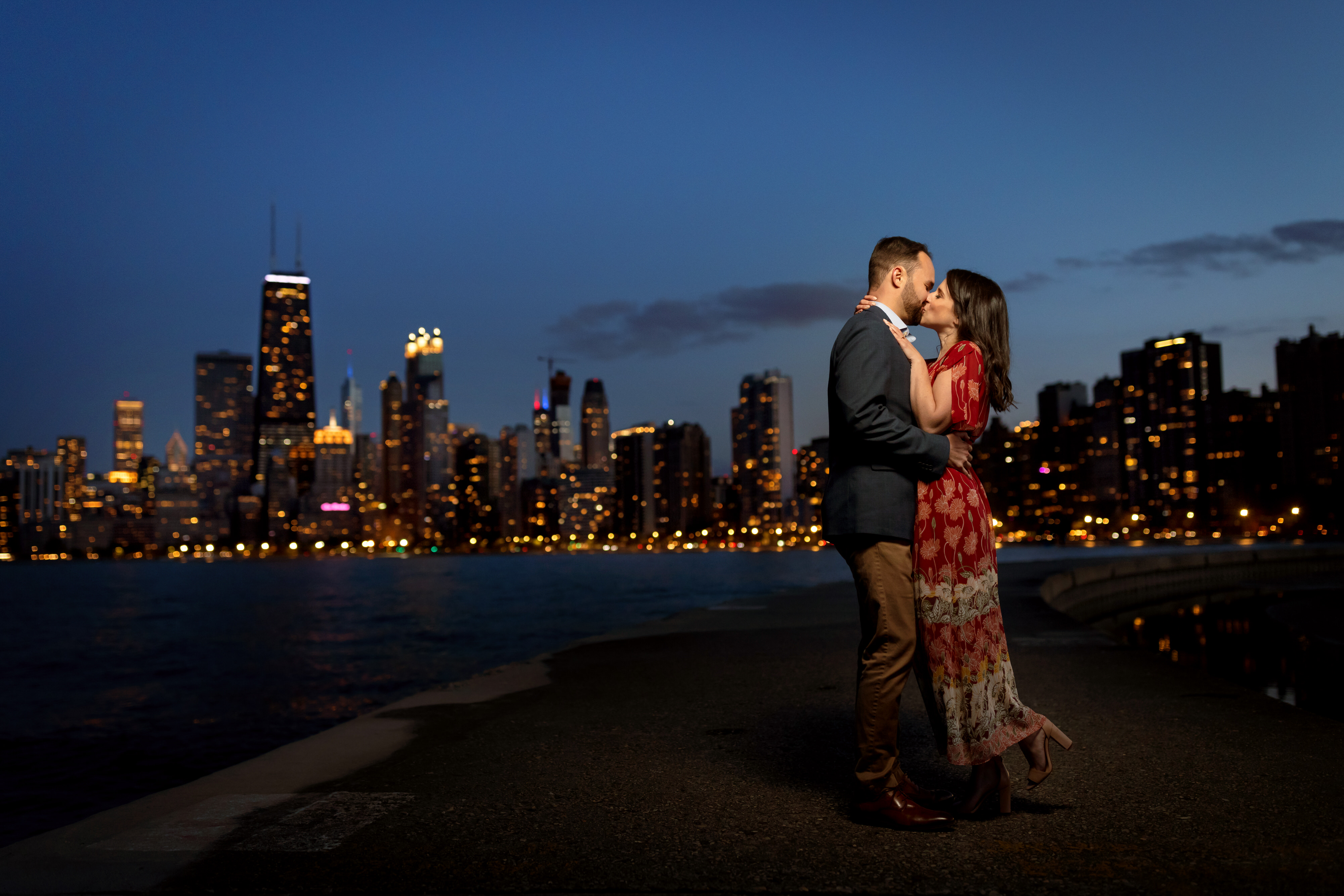 Couple poses for a portrait on the pier at North Avenue Beach in Chicago's Old Town neighborhood during an engagement session with the skyline in the background