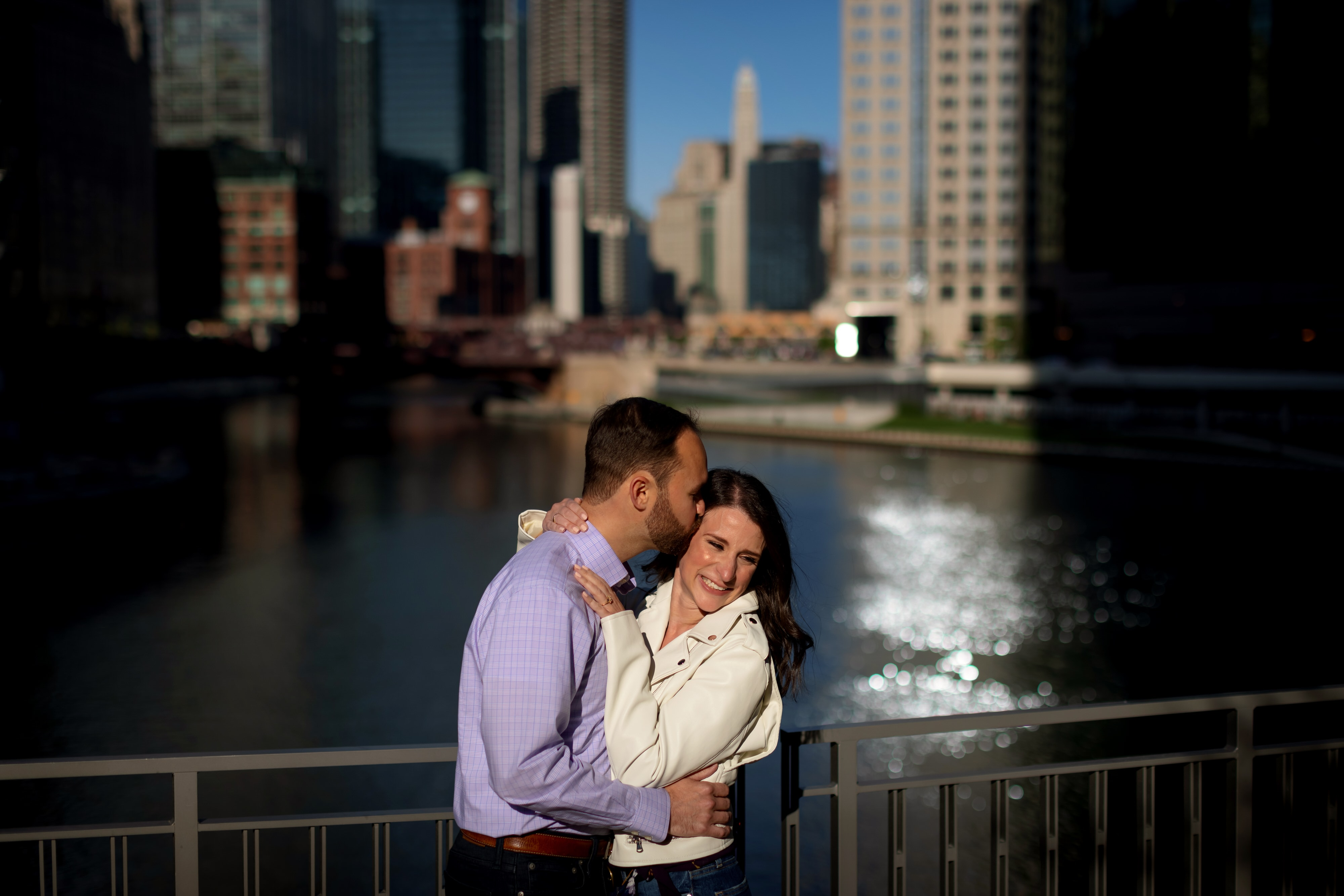 couple poses for engagement photos with Chicago river in background at Wolf Point near Gibson's Italia