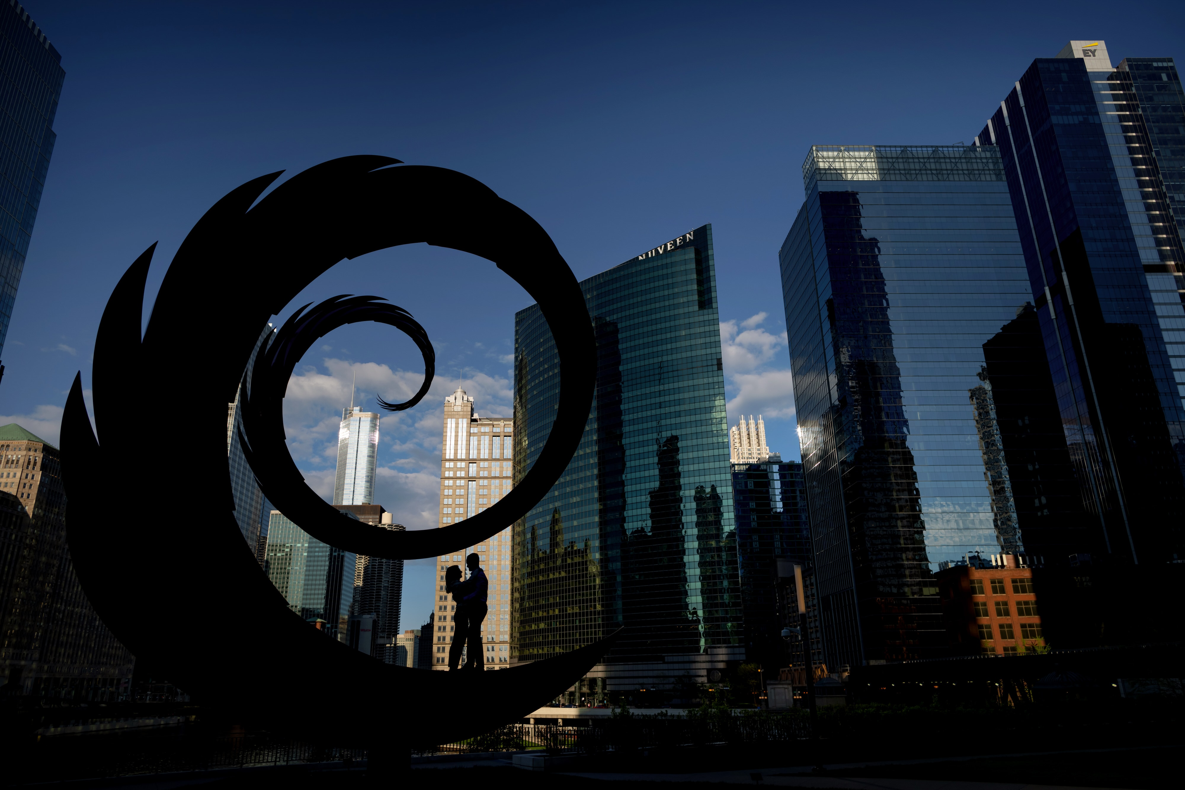 Couple is silhouetted against the Chicago skyline while standing on a sculpture at Wolf Point near Gibson's Italia and the Chicago River