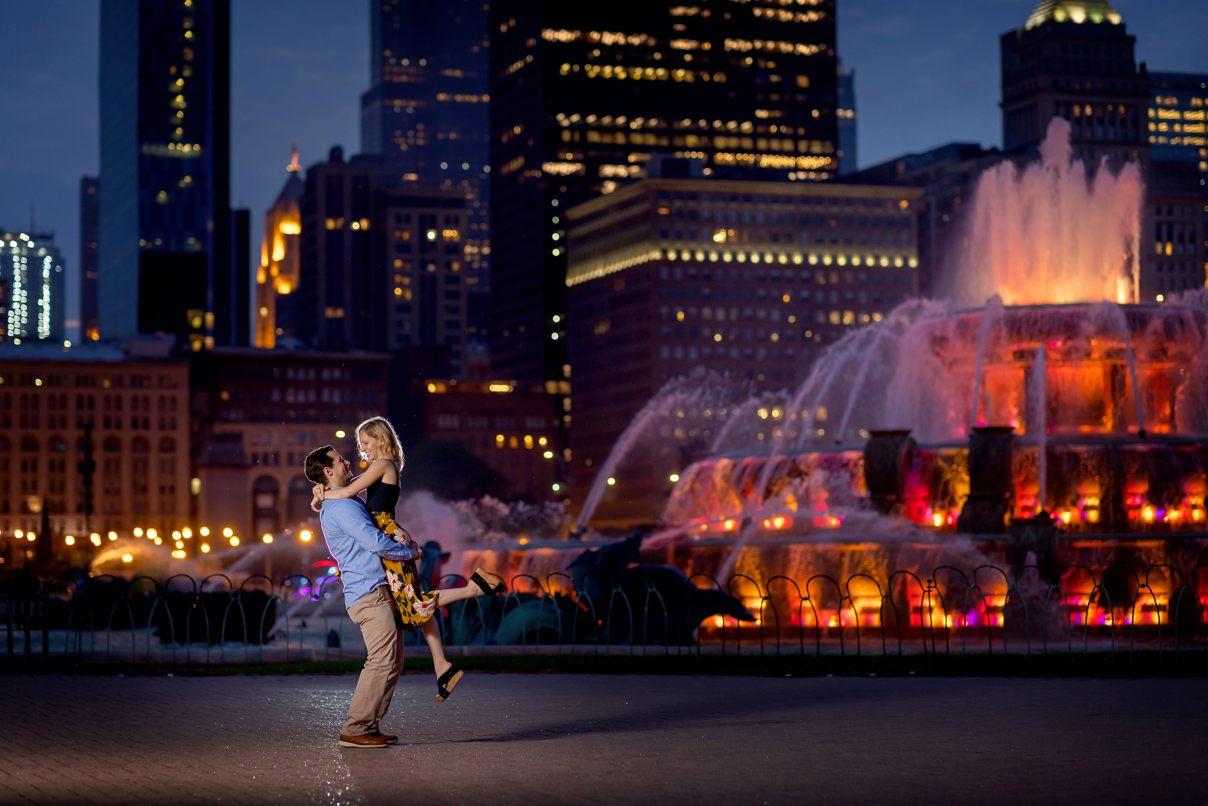 Twilight photo of couple backlit in front Buckingham Fountain in Grant Park during a Chicago engagement session