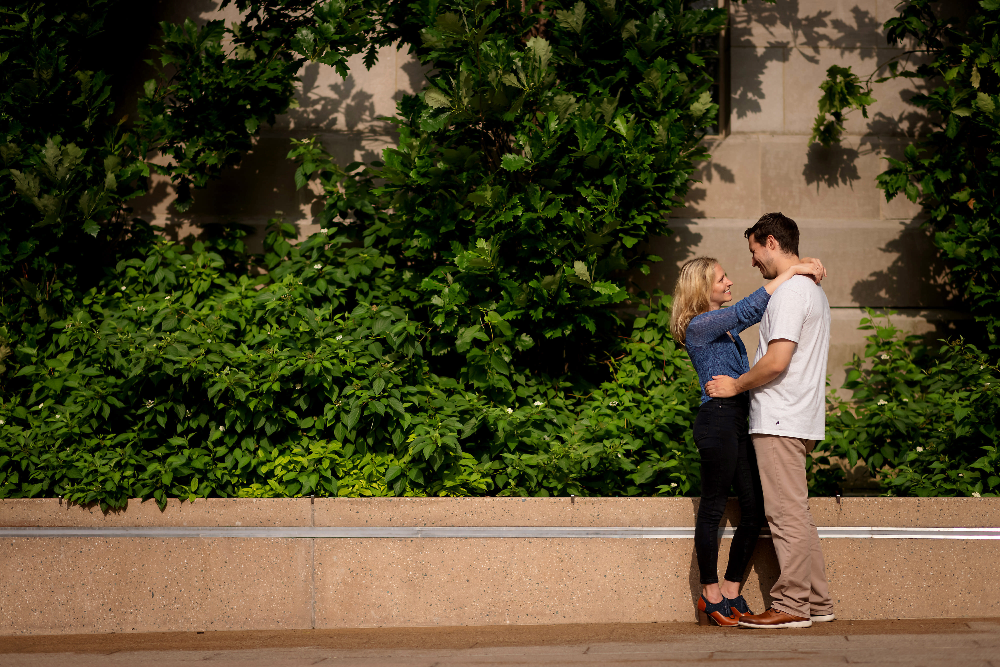 Couple poses for engagement pictures in front of ivy wall on the Chicago Riverwalk