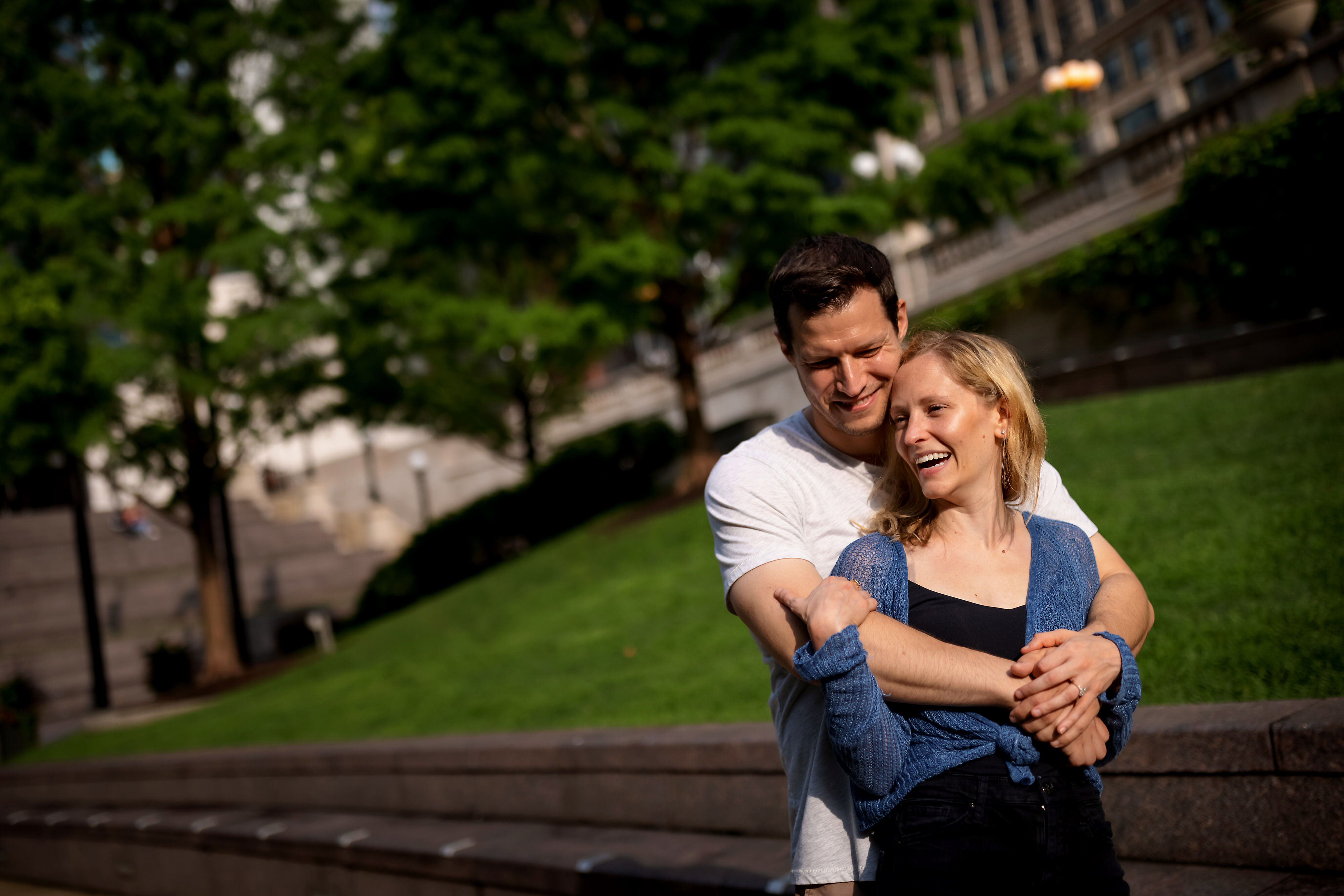 Couple poses for engagement pictures with trees and grassy hill in the background on the Chicago Riverwalk