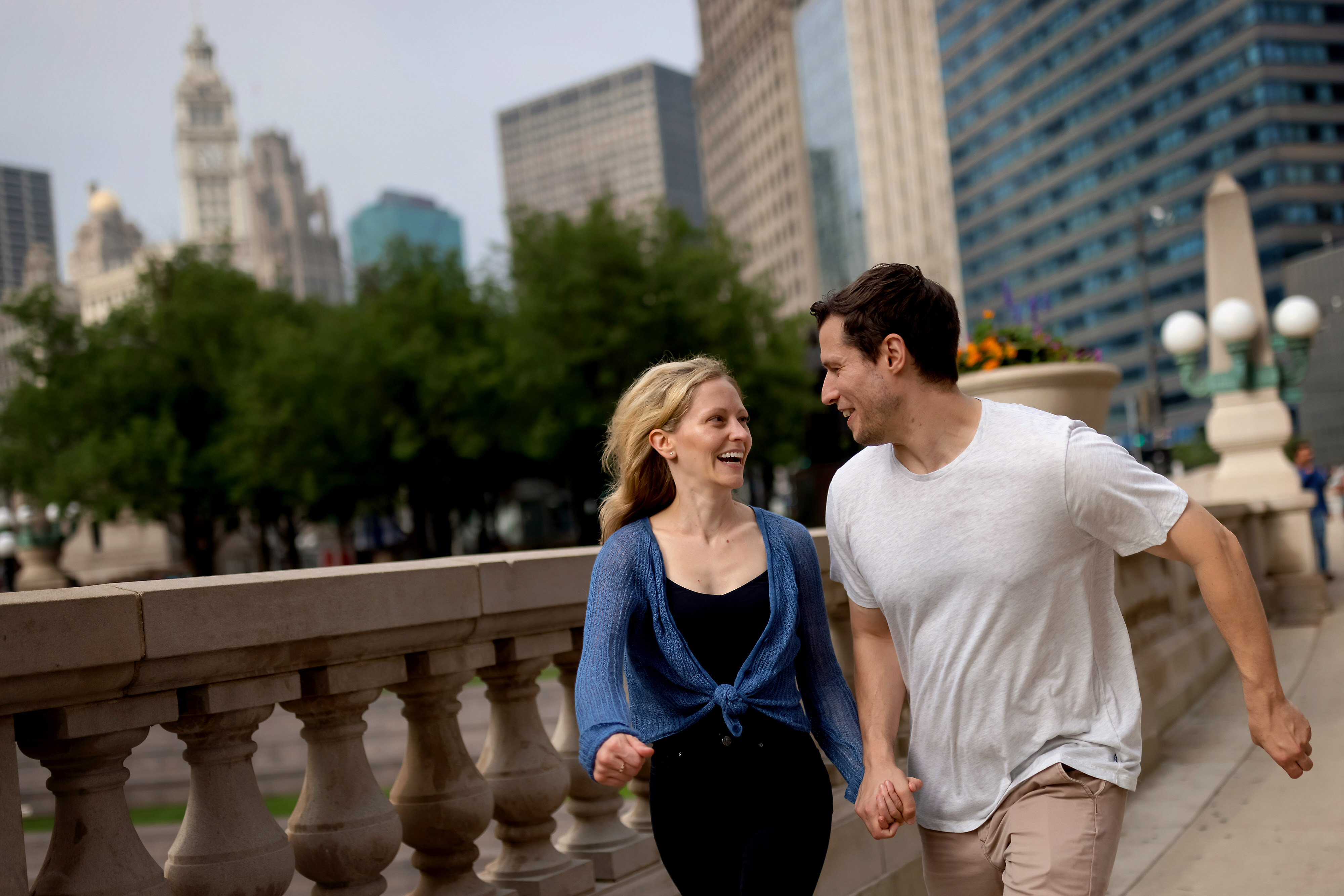 Couple runs along the Chicago Riverwalk with the Wrigley Building in the background during engagement session