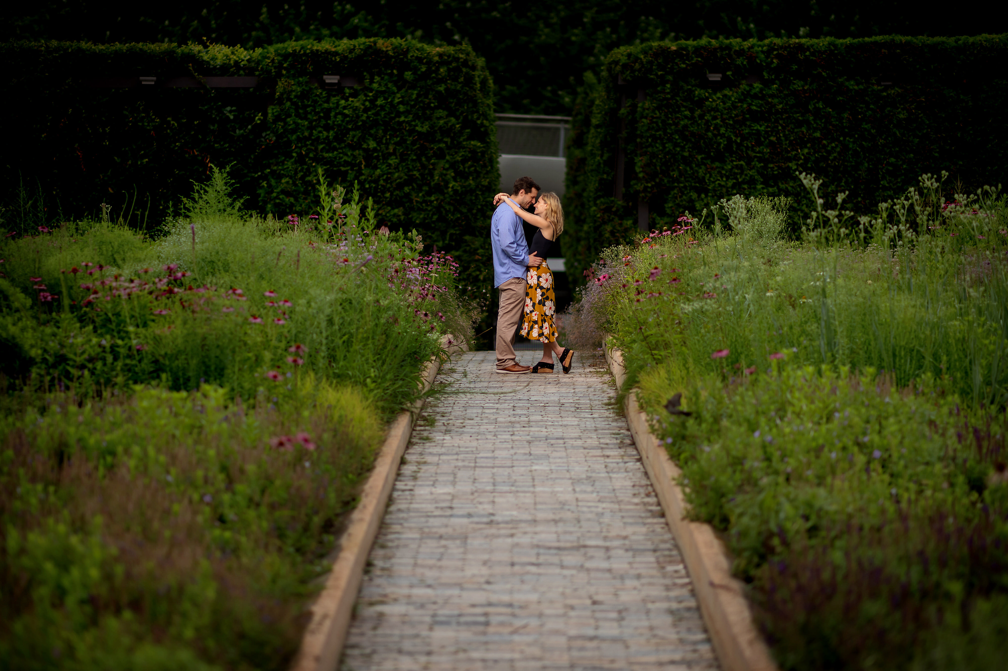Couple poses with arms around each other during engagement session in Lurie Garden