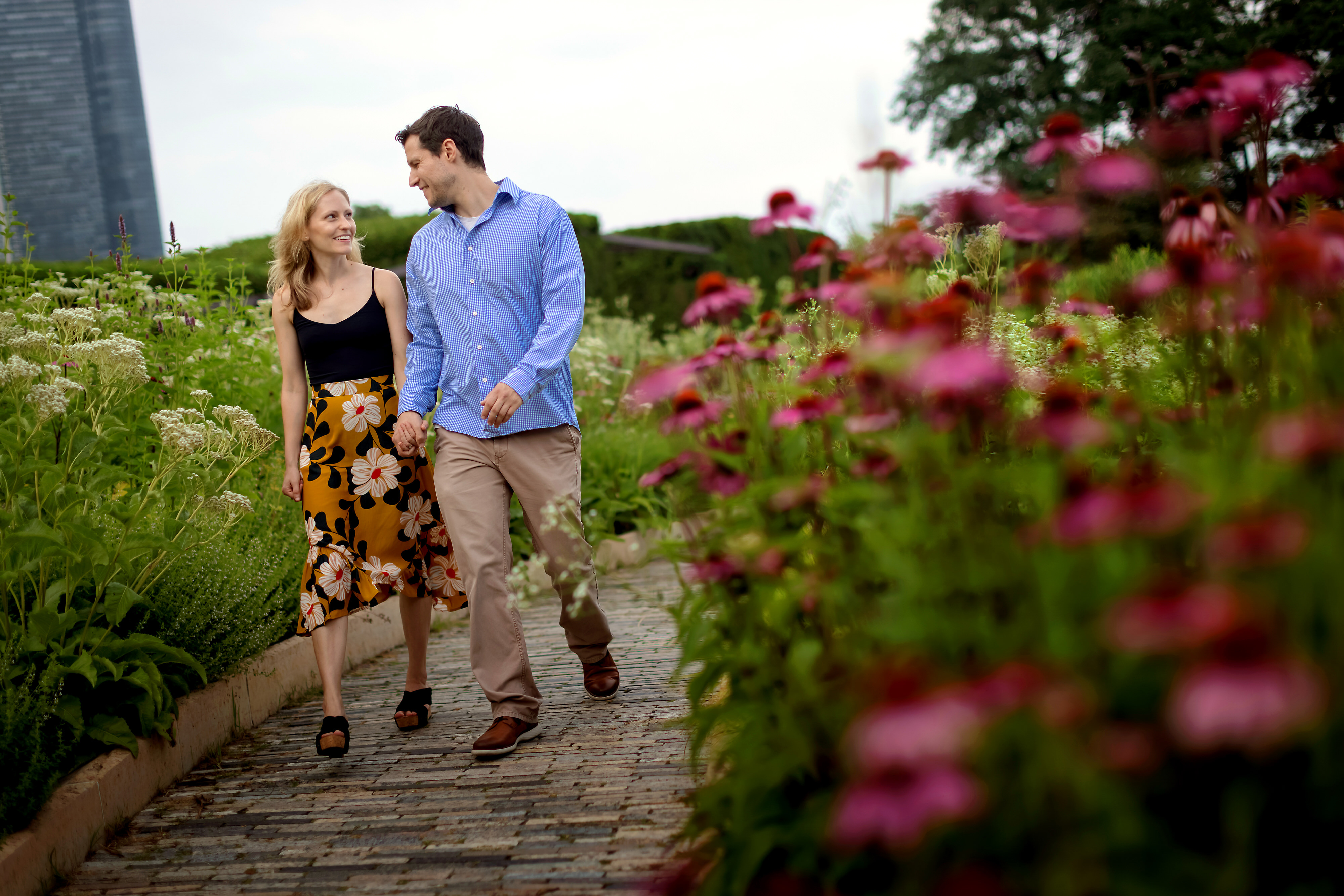 Couple walks through Lurie Garden during engagement session with pink flowers in the foreground