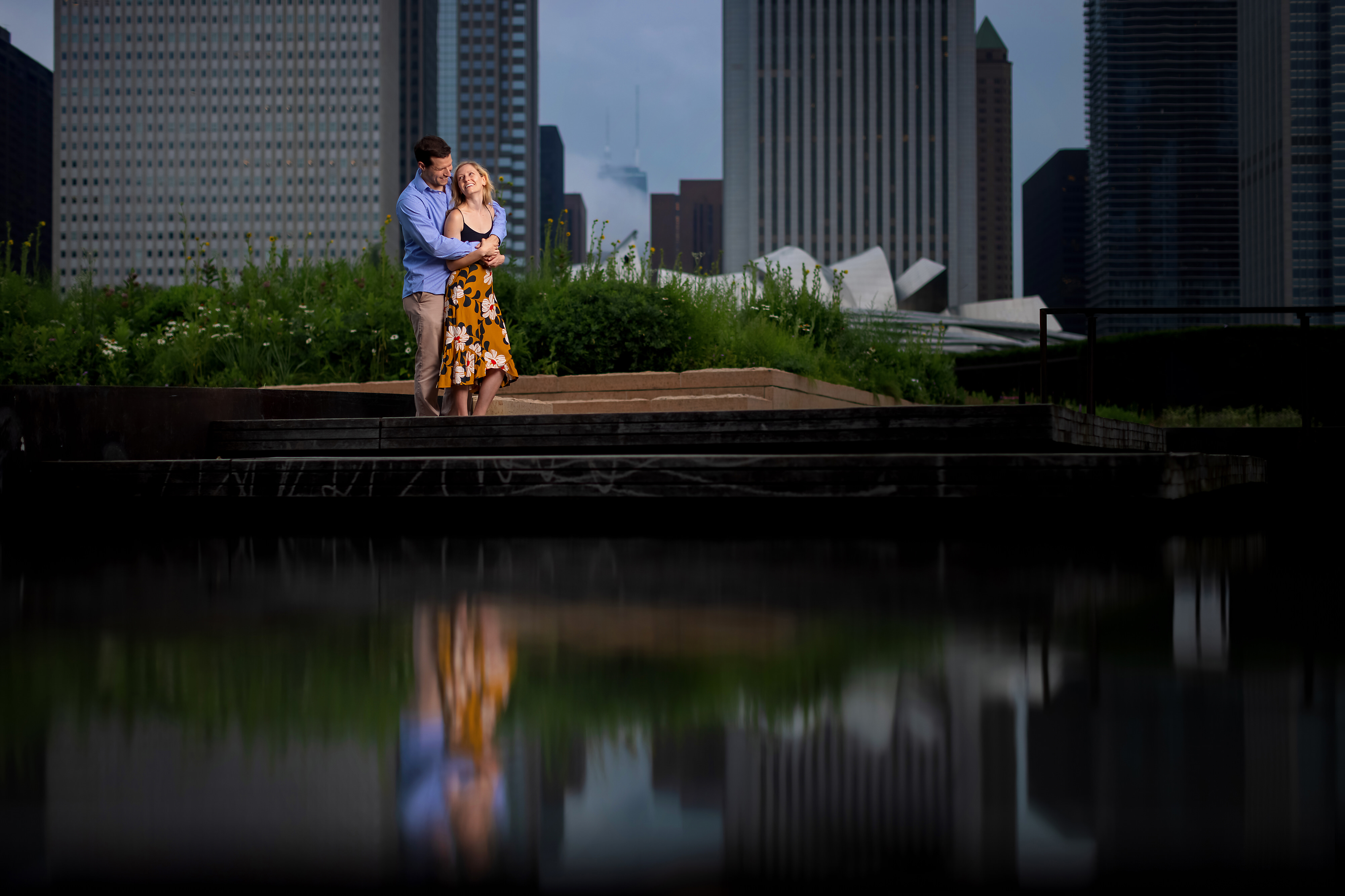 Couple poses with reflection pond and Hancock building in the background during engagement session in Lurie Garden