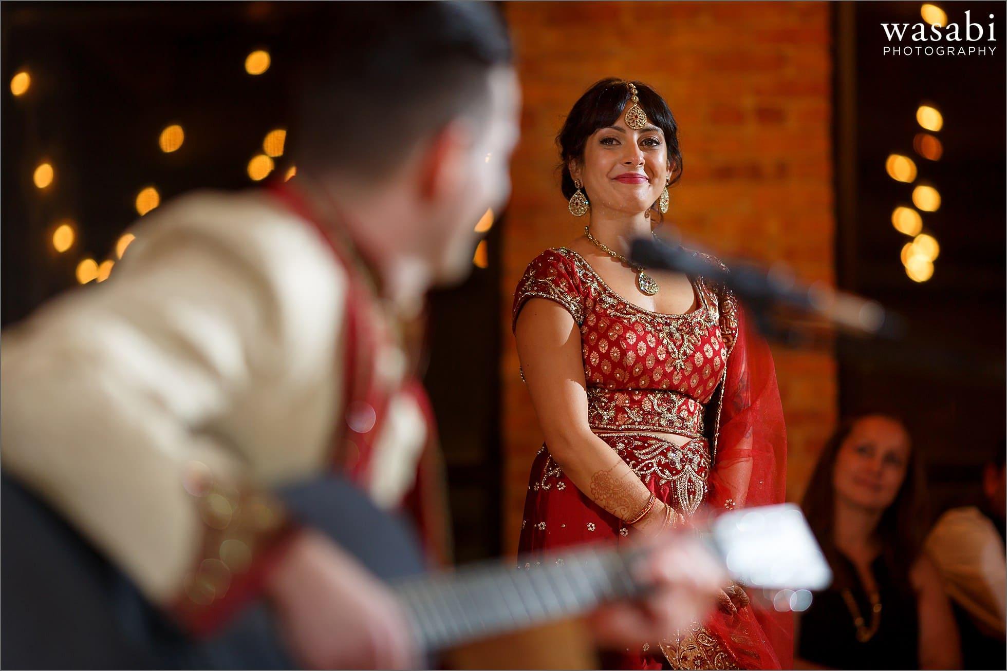 groom performs song guitar wedding reception