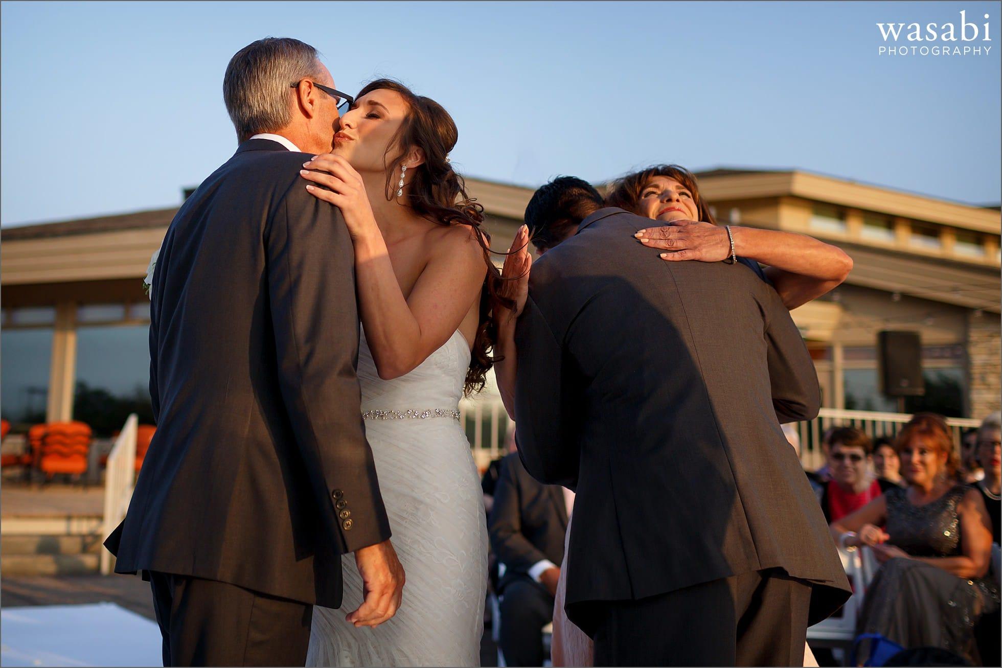 bride and groom hug parents