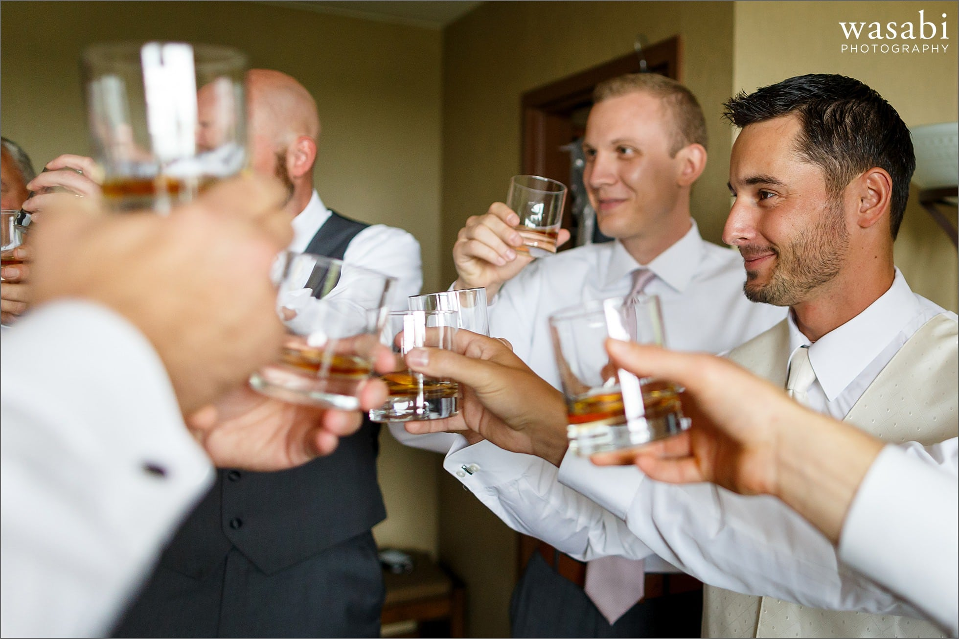 groom cheers with groomsmen